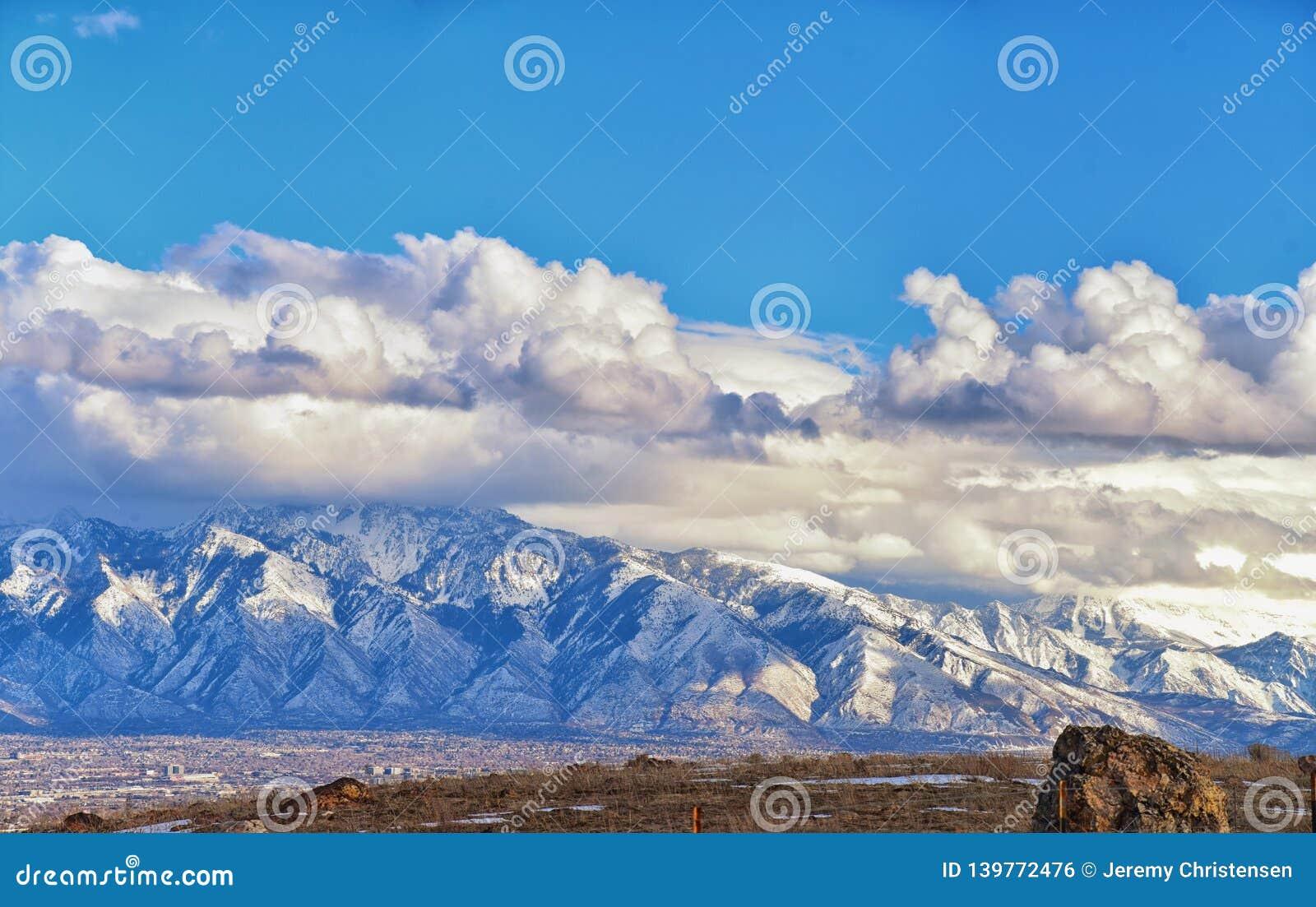 A vista panorâmica do inverno da neve tampou Wasatch Front Rocky Mountains, vale de Great Salt Lake e Cloudscape de Bacchus Highw