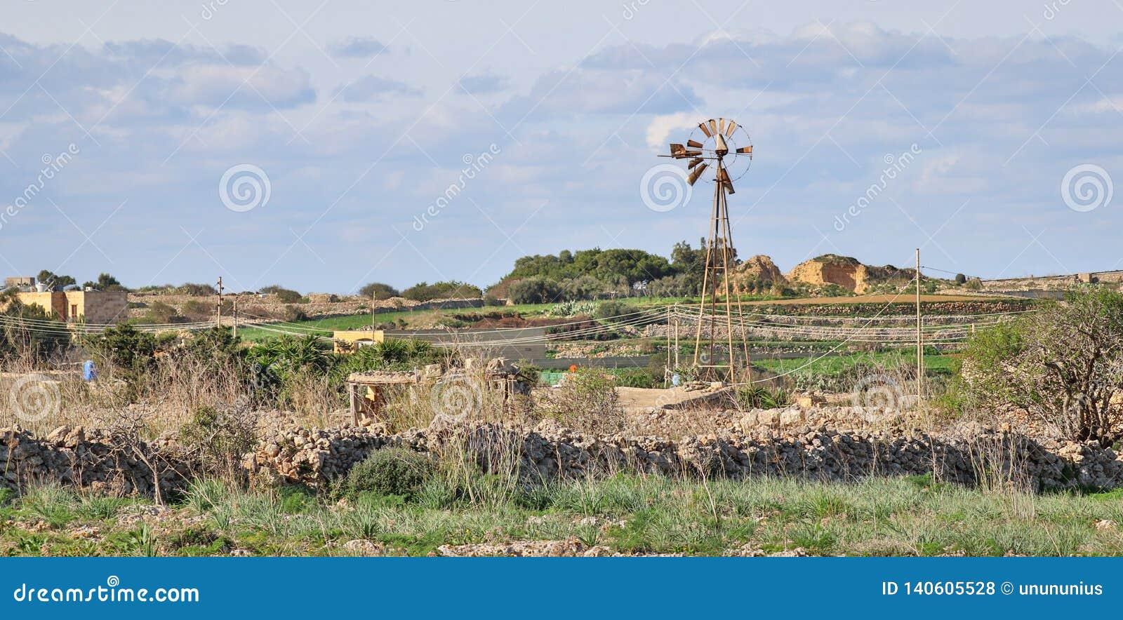 Vista panorâmica em uma paisagem ocidental selvagem bonita com paredes de pedra, casa de campo e um moinho de vento quebrado em D