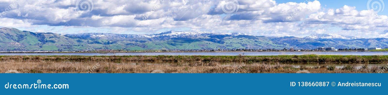 Vista panorâmica para montes verdes e montanhas nevados em um dia de inverno frio tomado das costas de um pântano no sul San