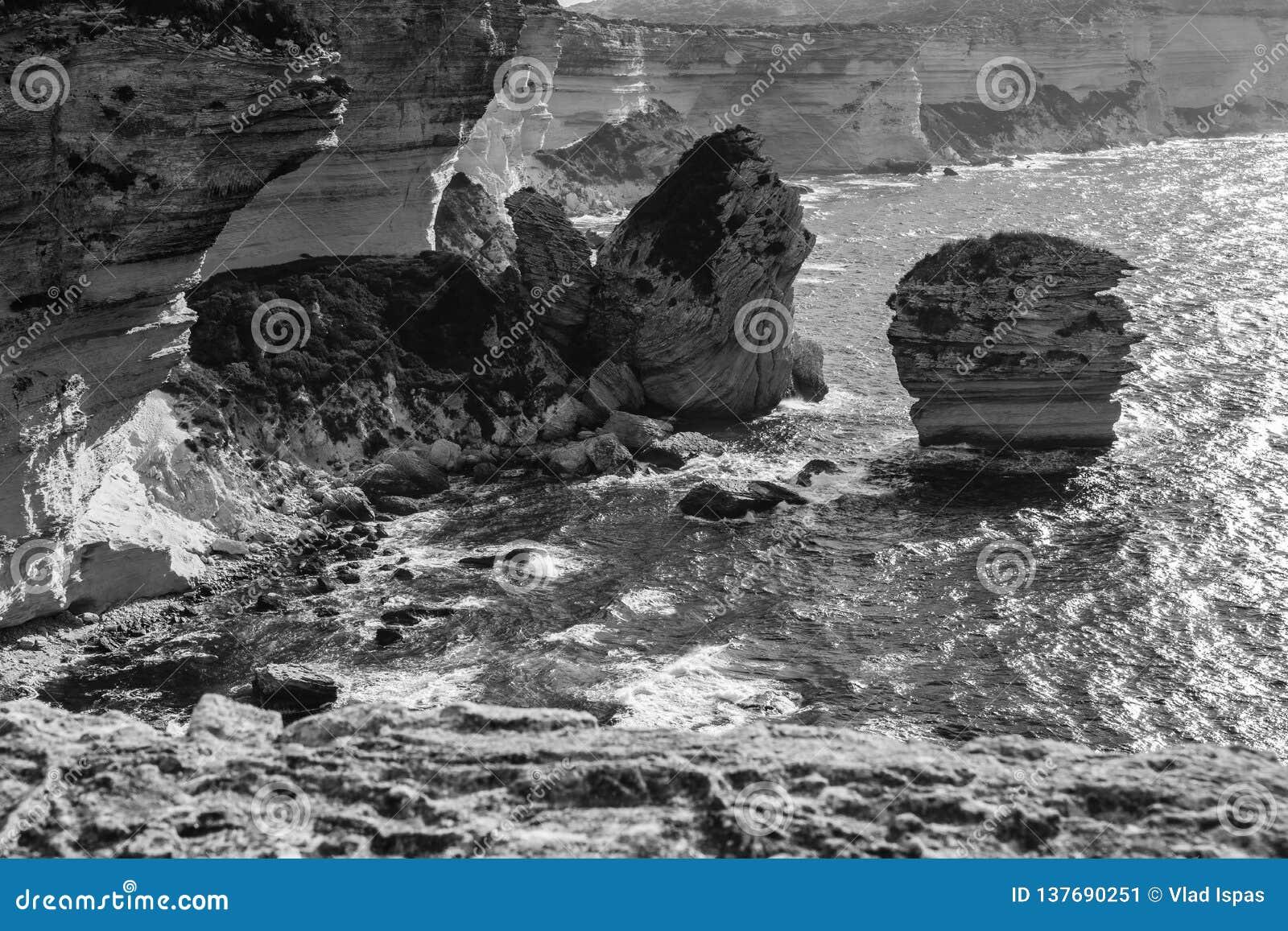 Vista panorâmica preto e branco da costa de mar rochosa do thr com água azul transparente clara, penhascos, rochas enormes, grama