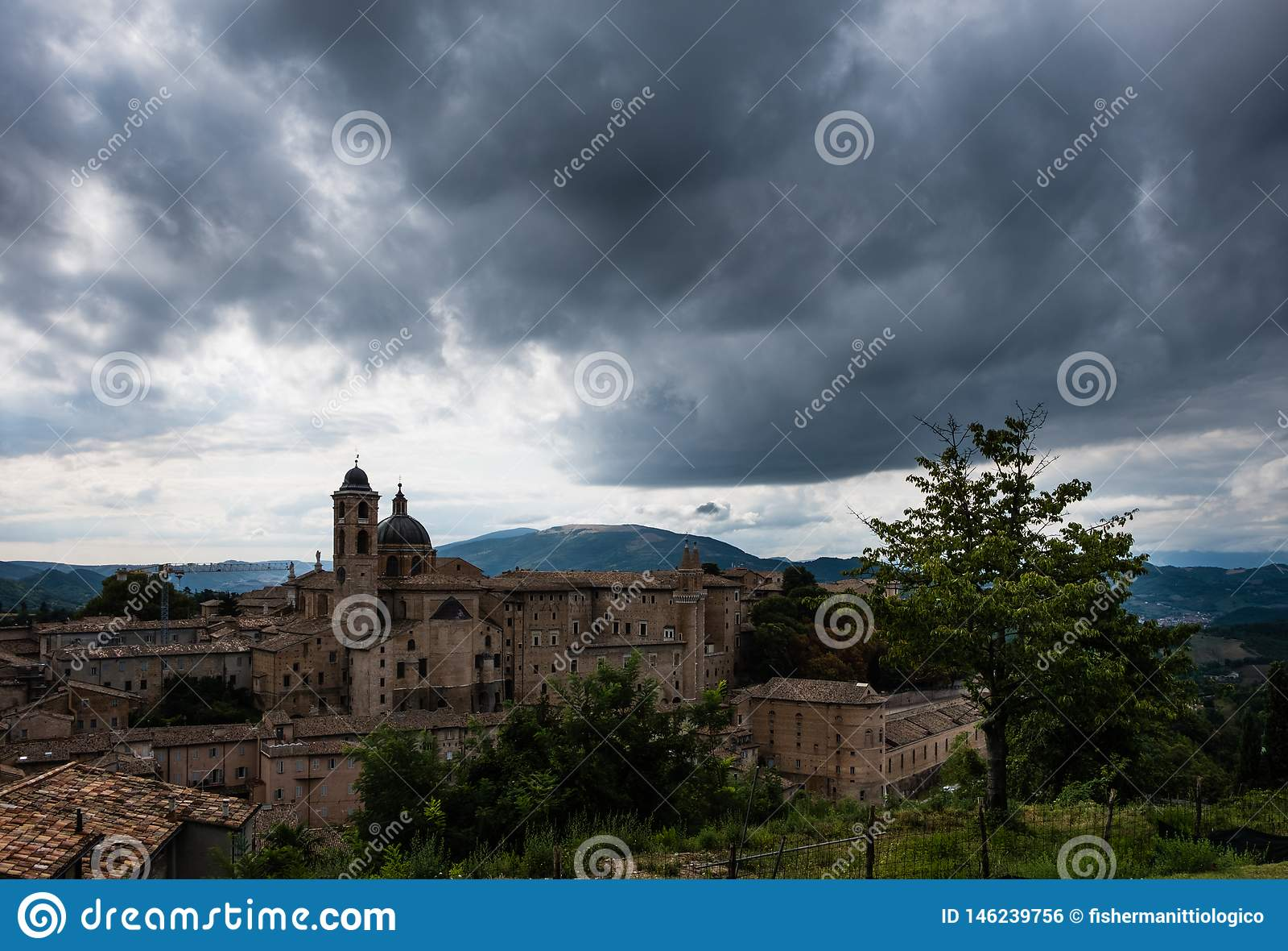 Vista panor?mica do pal?cio ducal de Urbino em It?lia central com um c?u dram?tico