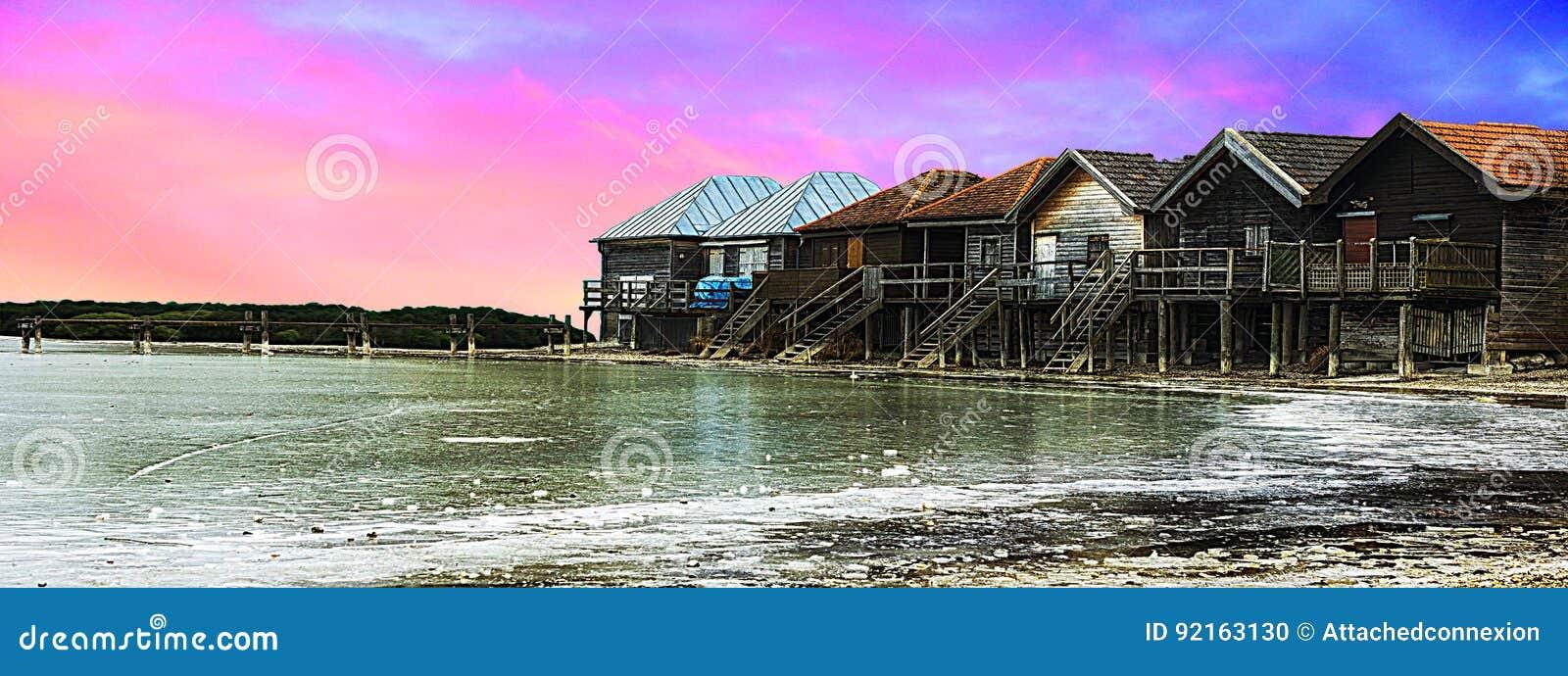 Vista panoramica, bello fiume, vecchie case di legno sopra il cielo variopinto e nuvole