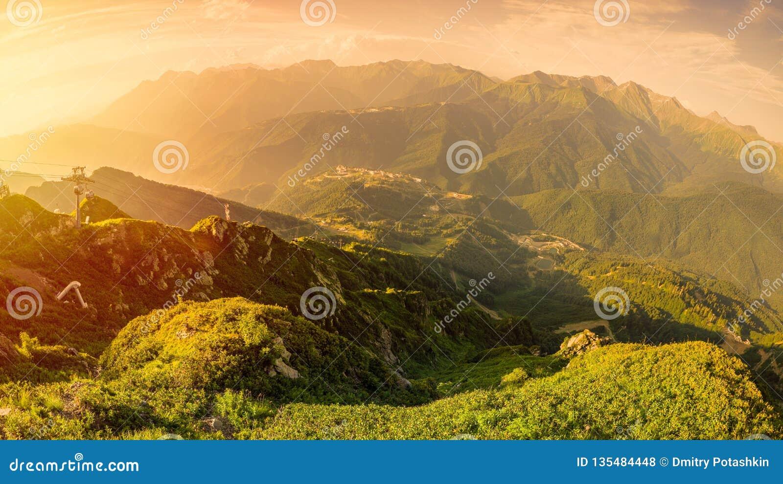 Vista panoramica del tramonto di estate dalla cima della gamma di Aibga alla stazione sciistica Rosa Khutor La cabina di funivia
