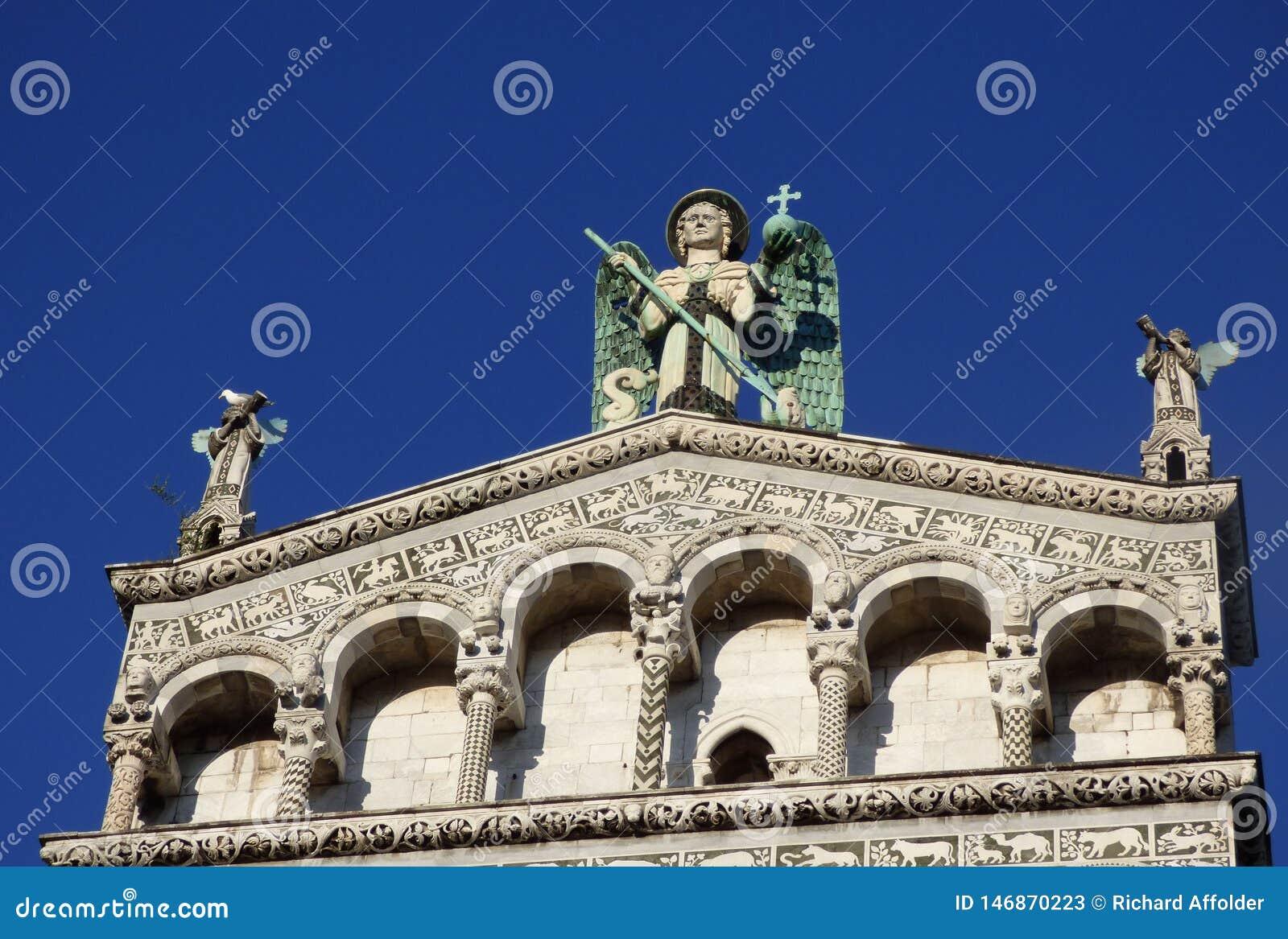 Vista para cima na fachada de uma catedral com estátuas angélicos e um fundo do céu azul