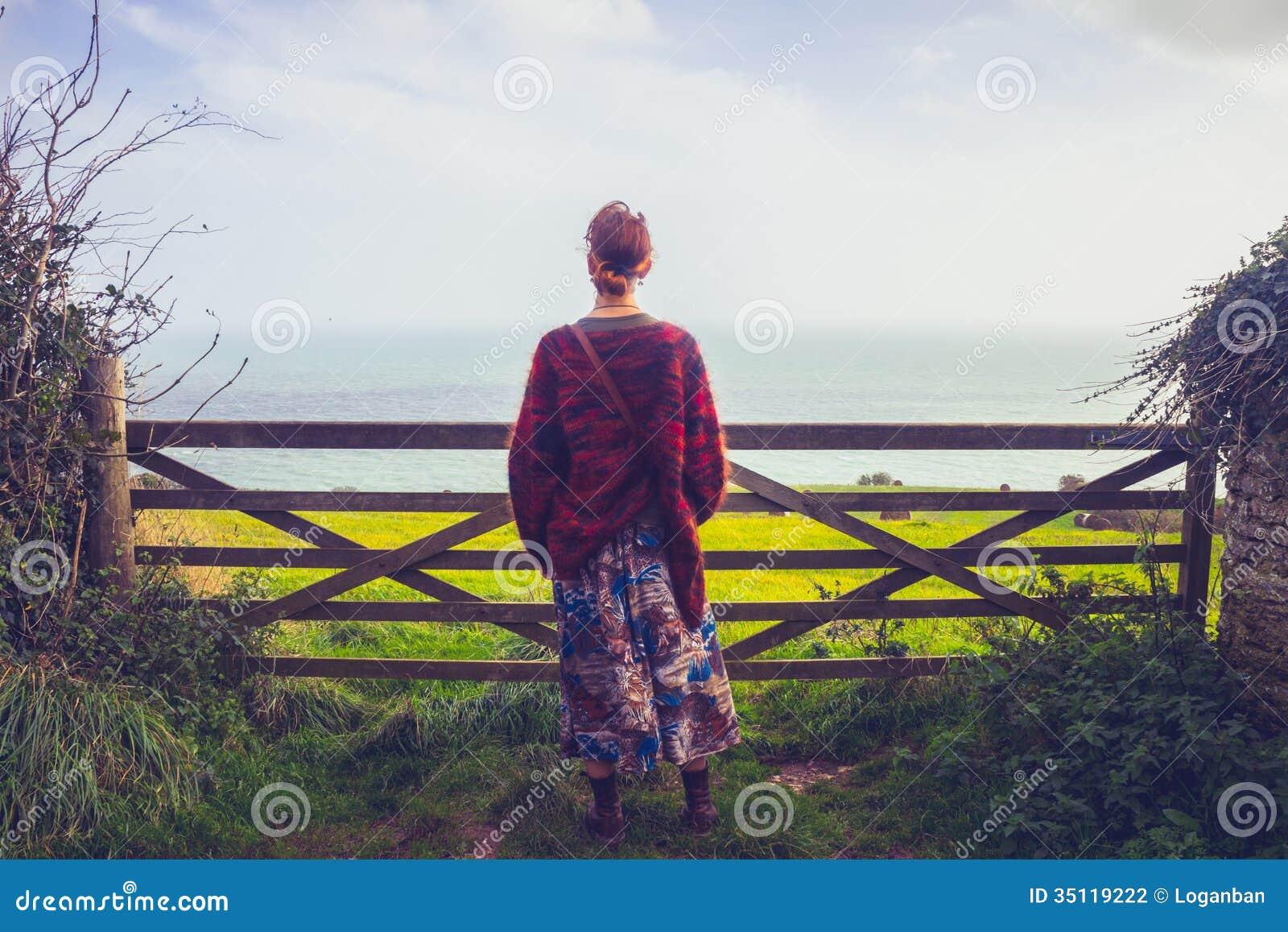 Vista piena d ammirazione del mare della giovane donna dal recinto rurale