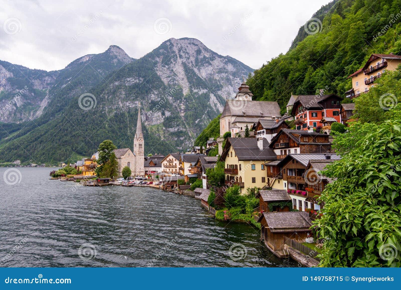 Vista pitoresca da vila de Hallstatt, situada no banco do lago Hallstatter, montanhas altas dos cumes, Áustria