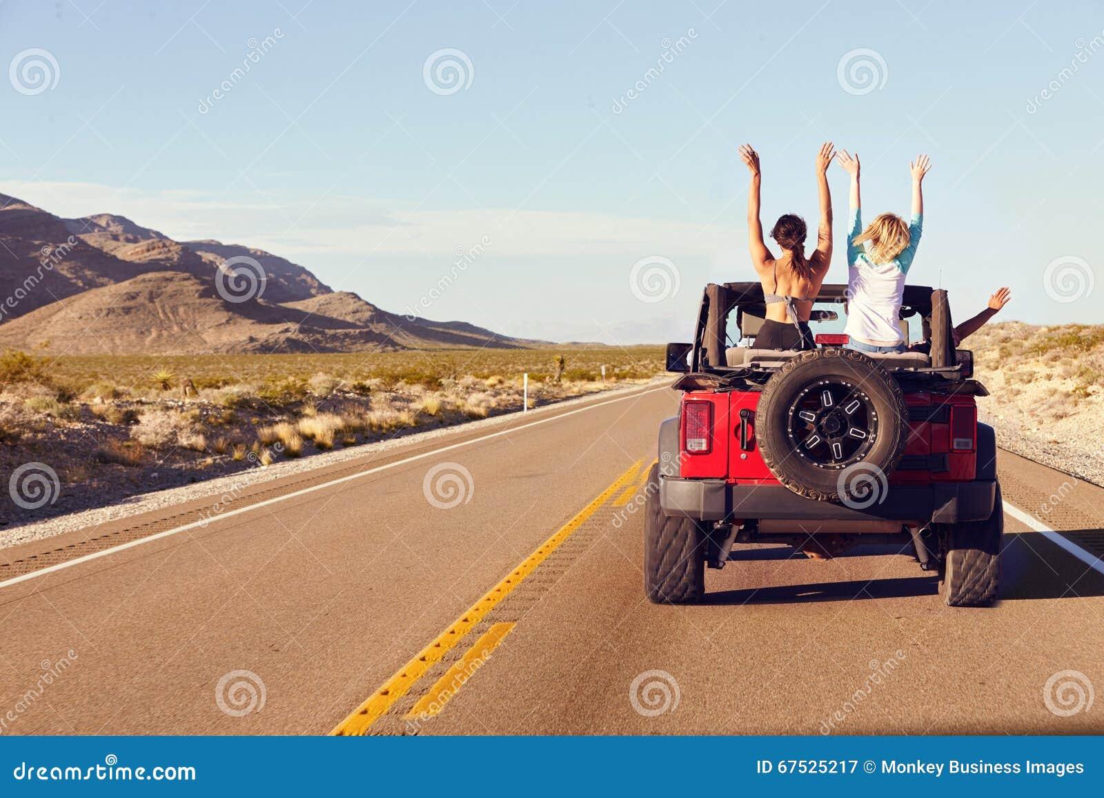 Vista posterior de amigos en el viaje por carretera que conduce en coche convertible