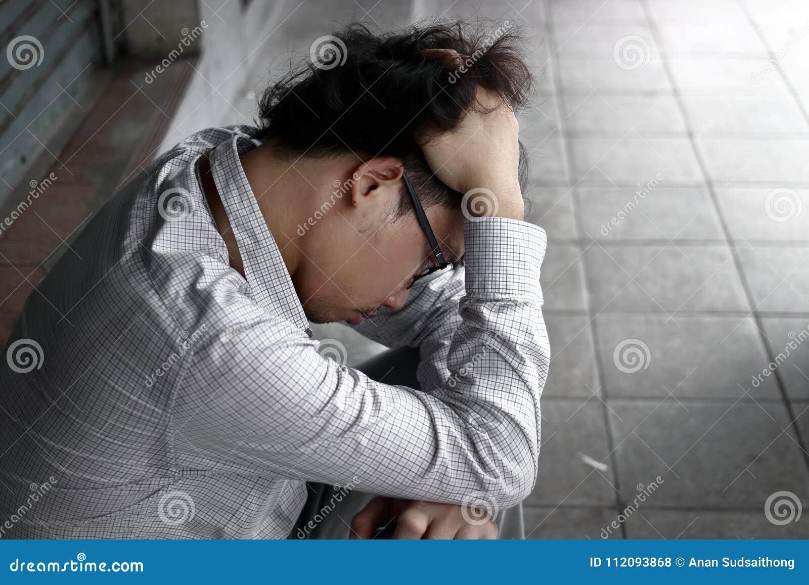 Vista posterior de la cara asiática joven de la cubierta del hombre de negocios de la ansiedad confusa con las manos