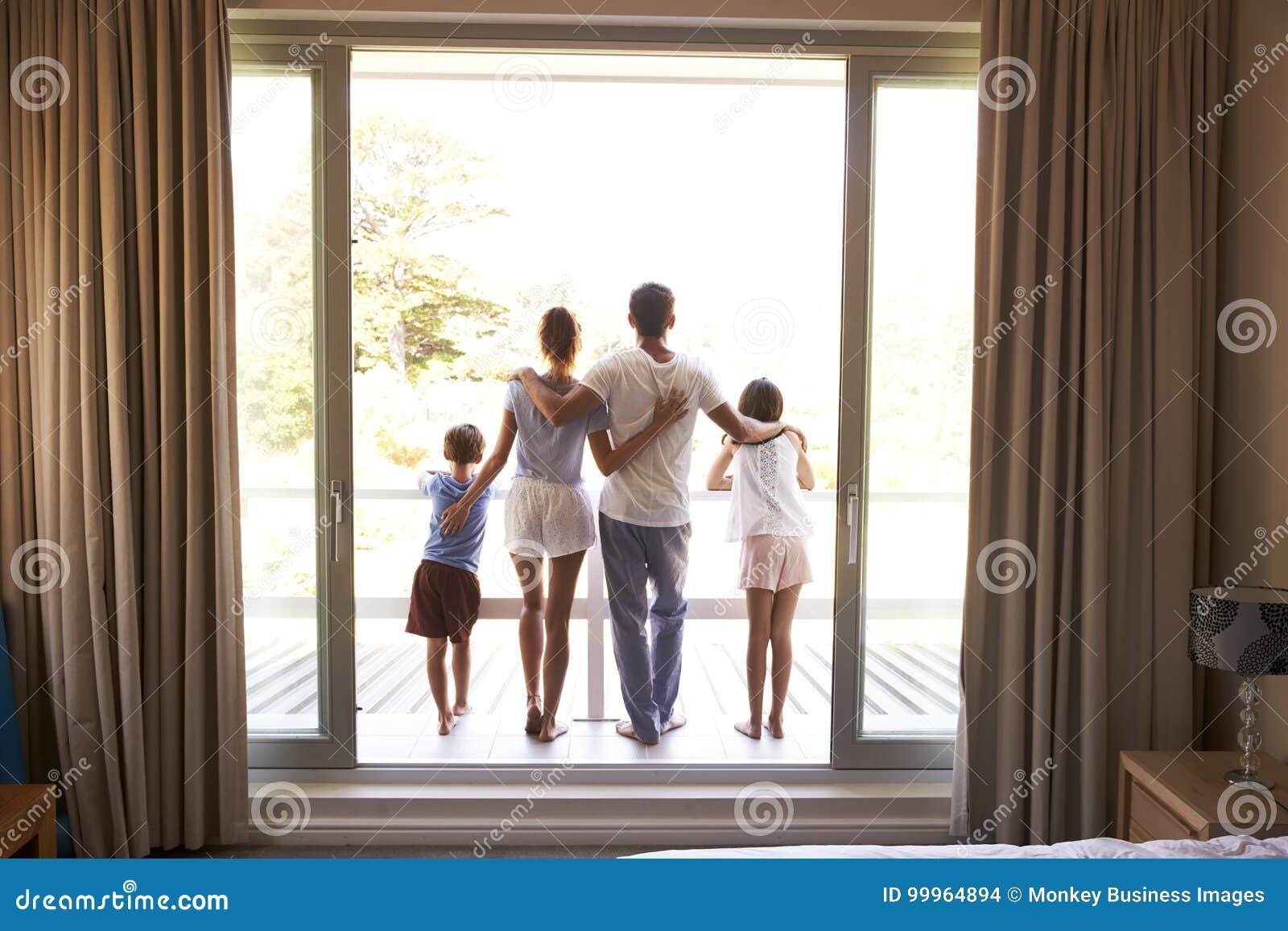 Vista posterior de la familia en el balcón que mira hacia fuera en nuevo día