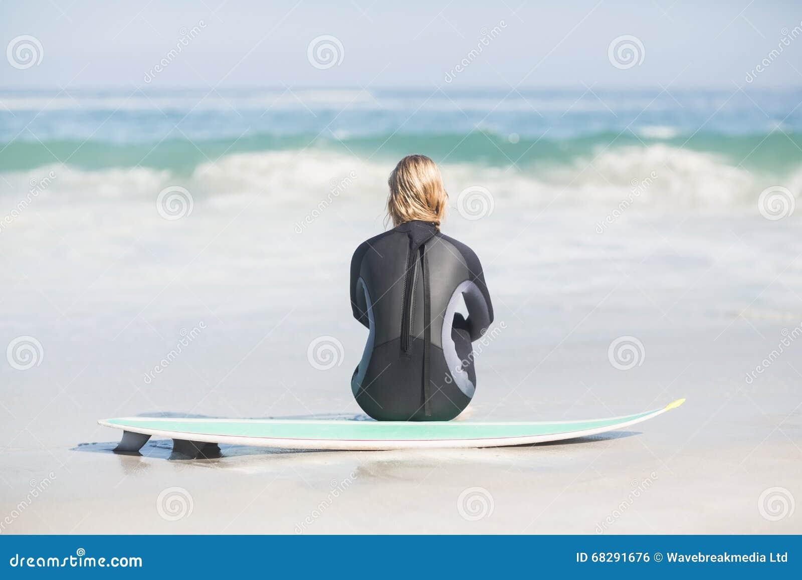 Vista posterior de la mujer en el wetsuit que se sienta con la tabla hawaiana en la playa