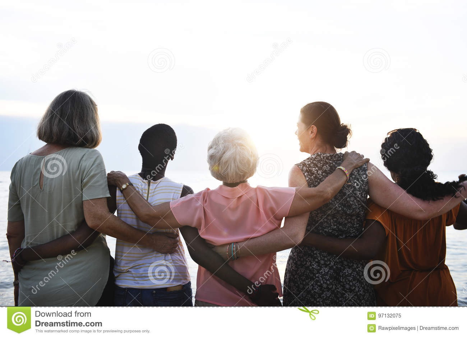 Vista posterior de las mujeres mayores diversas que se unen en la playa