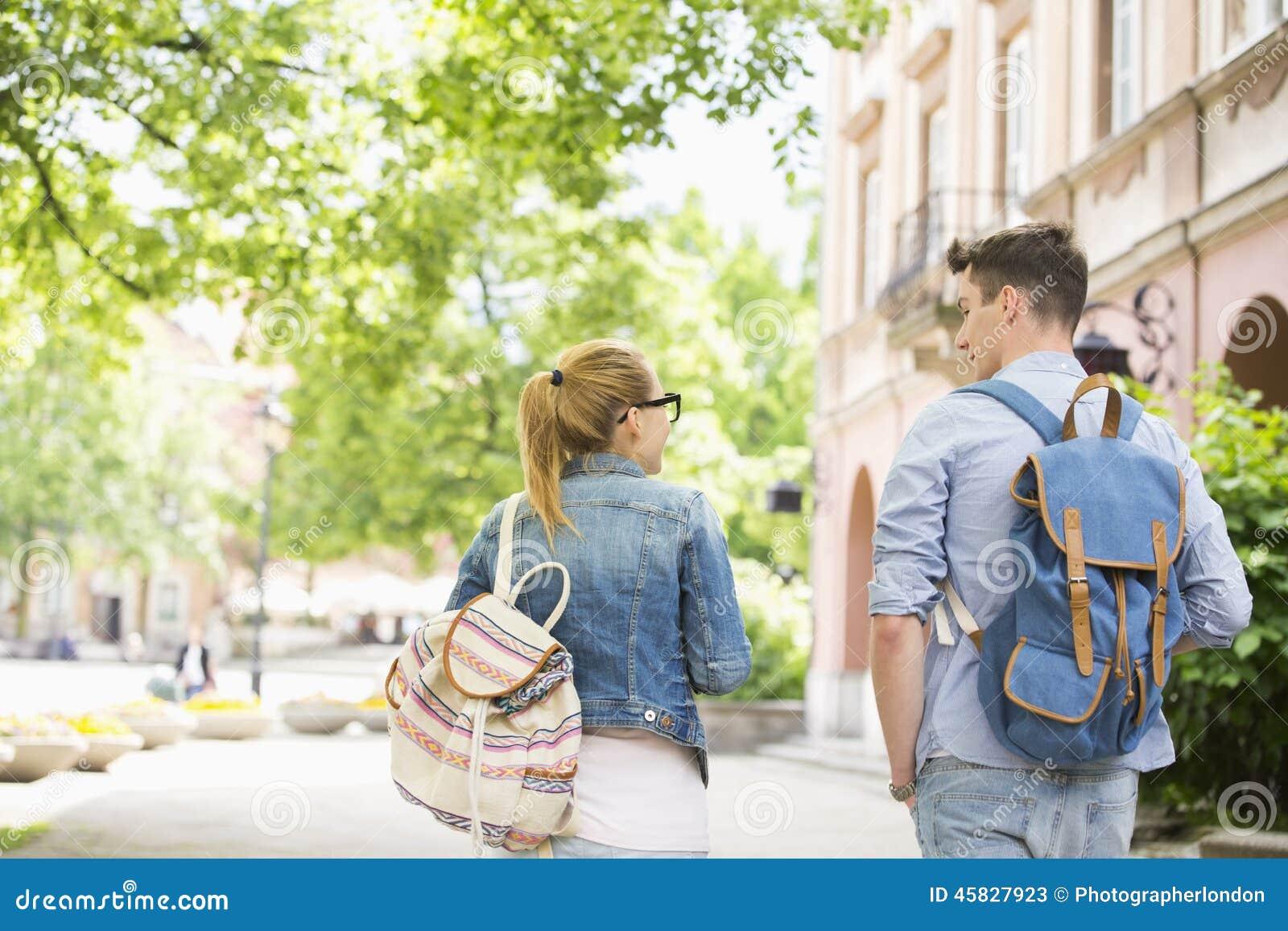 Vista posterior de los amigos jovenes de la universidad que hablan mientras que camina en campus