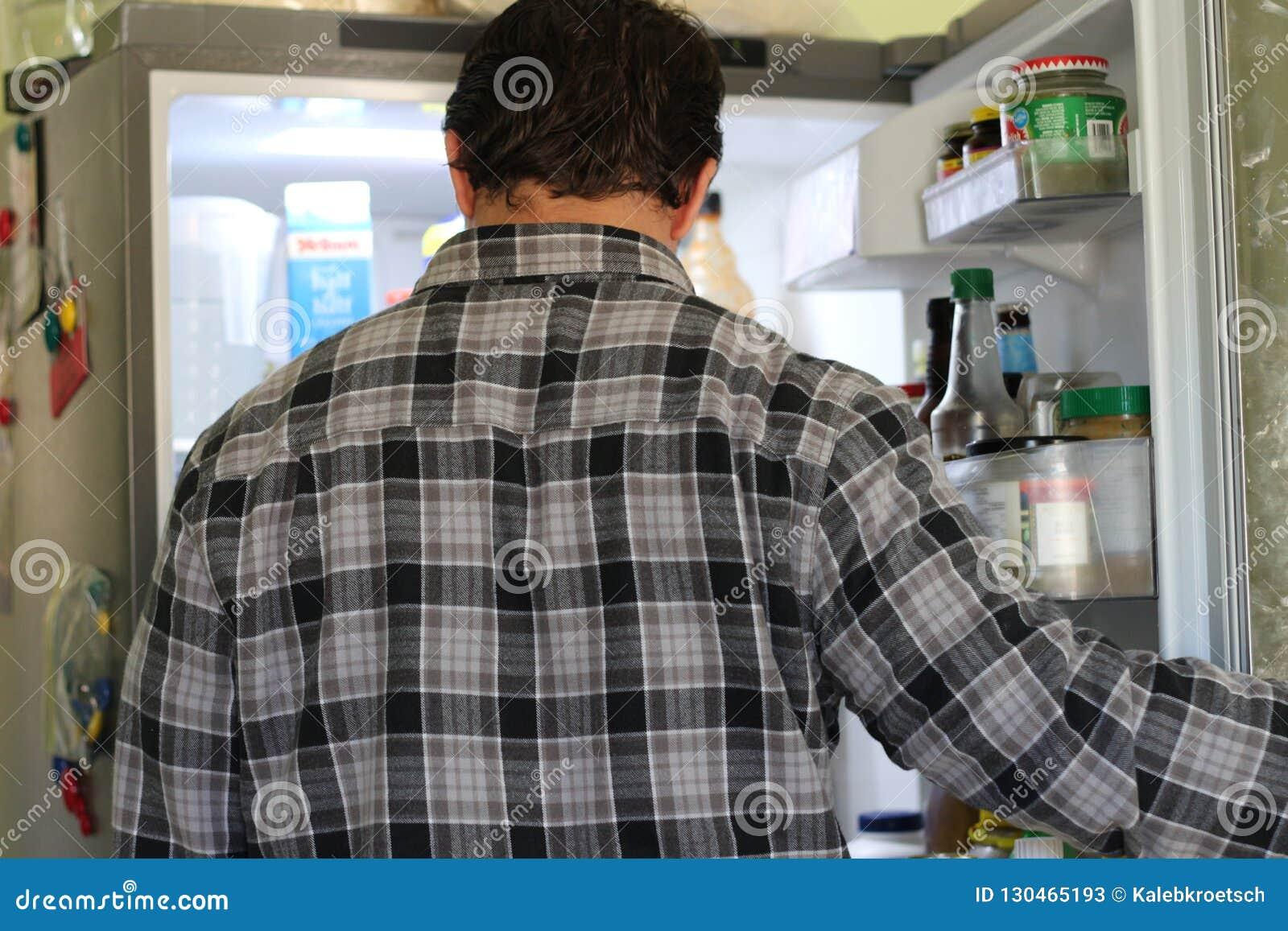 Vista posterior de un hombre joven confuso que mira la comida en refrigerador