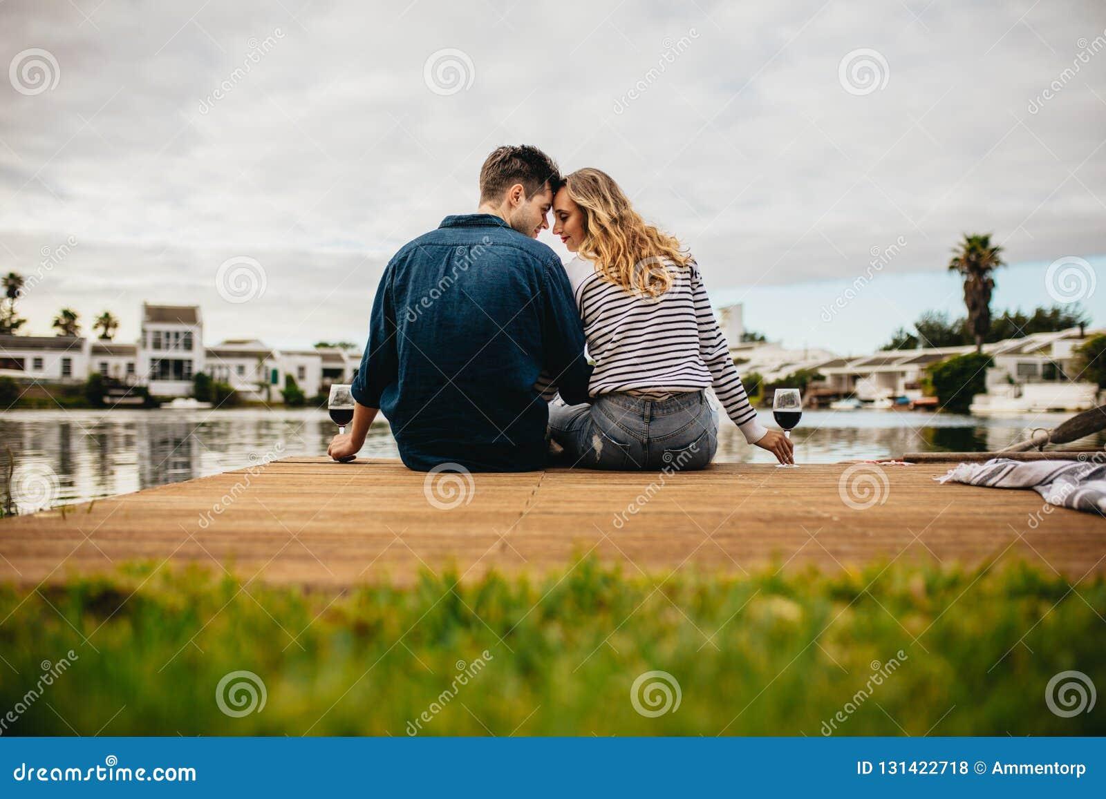 Vista posterior de un par en el amor que se sienta juntas tocando sus cabezas cerca de un lago Júntese en un día hacia fuera que