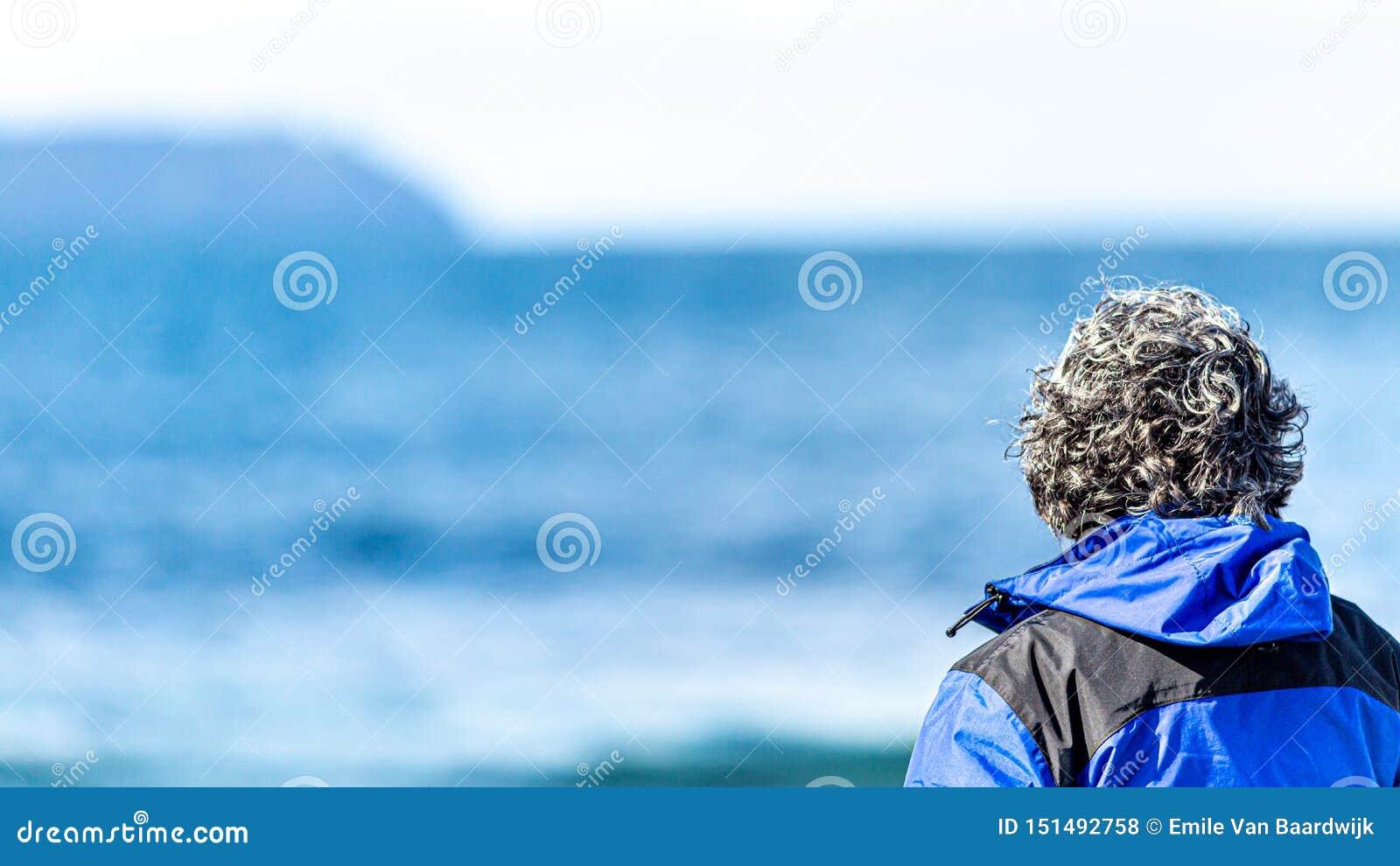 Vista posterior de una mujer madura con el pelo gris que mira el mar