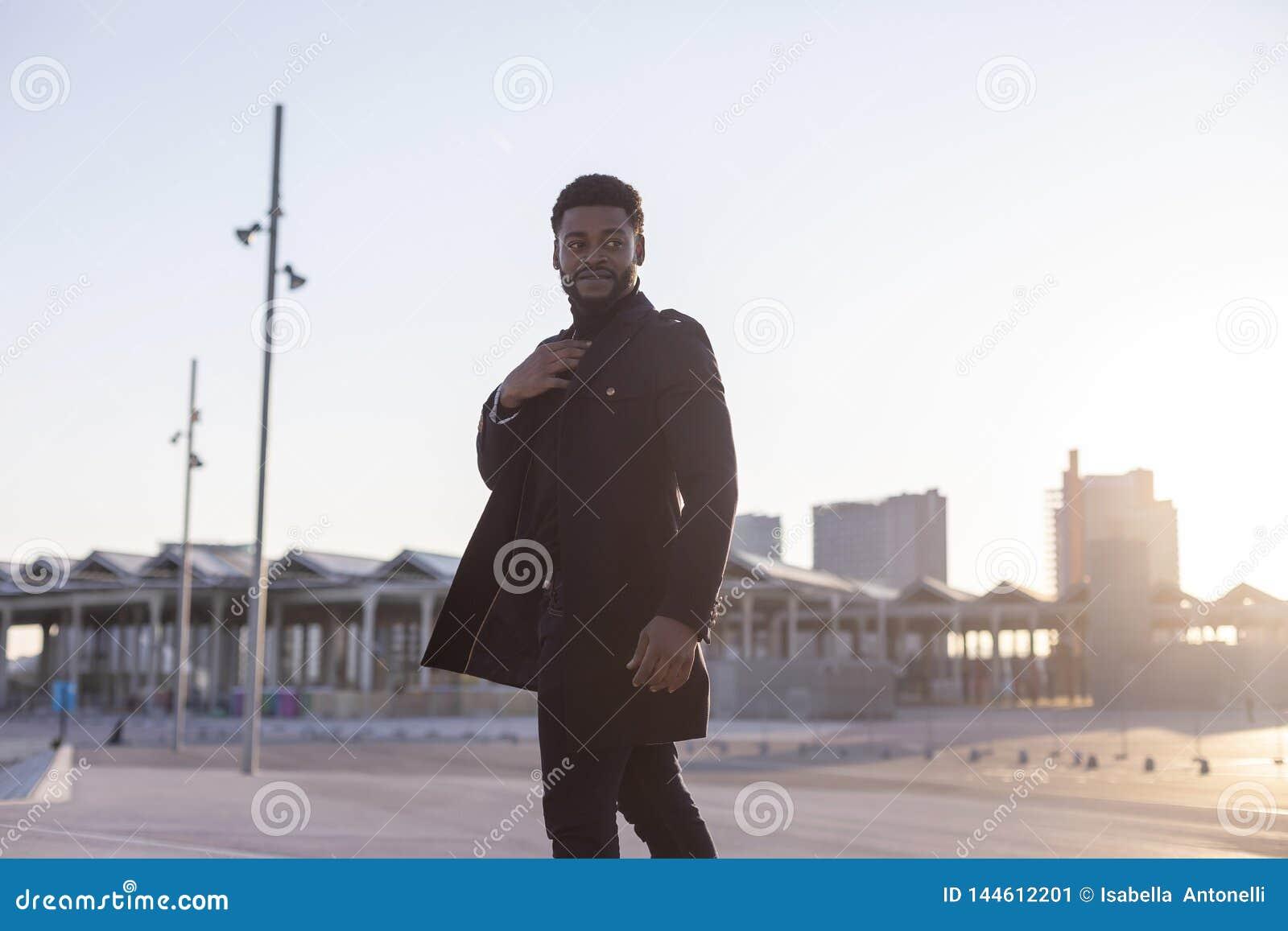 Vista posterior del hombre barbudo joven negro que camina al aire libre mientras que mira lejos