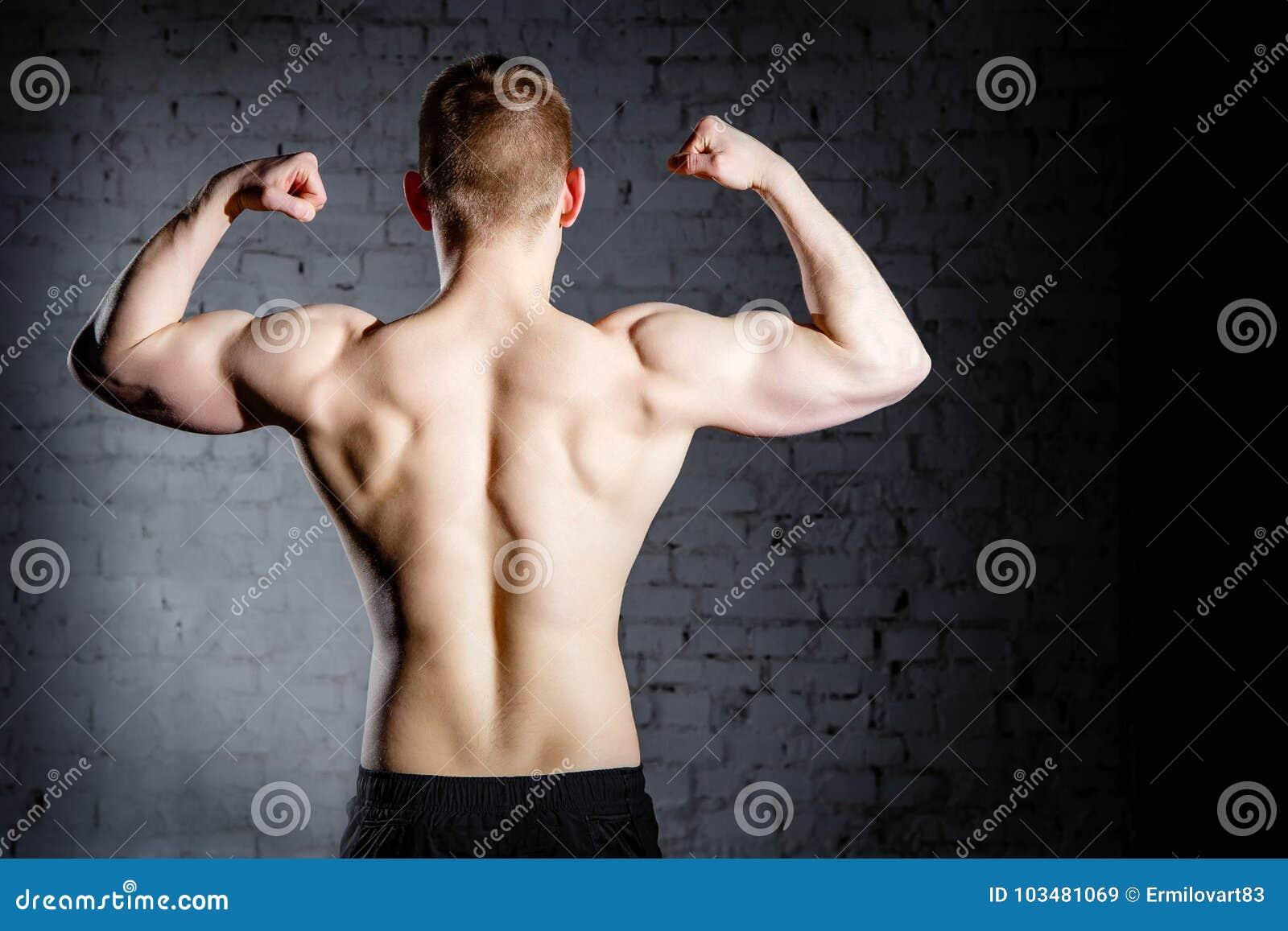 Vista posterior del hombre muscular caucásico atractivo joven del culturista con el cuerpo perfecto que se resuelve en centro de