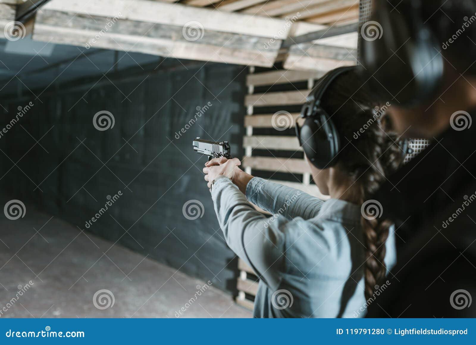 Vista posterior del tiroteo de la muchacha con el arma