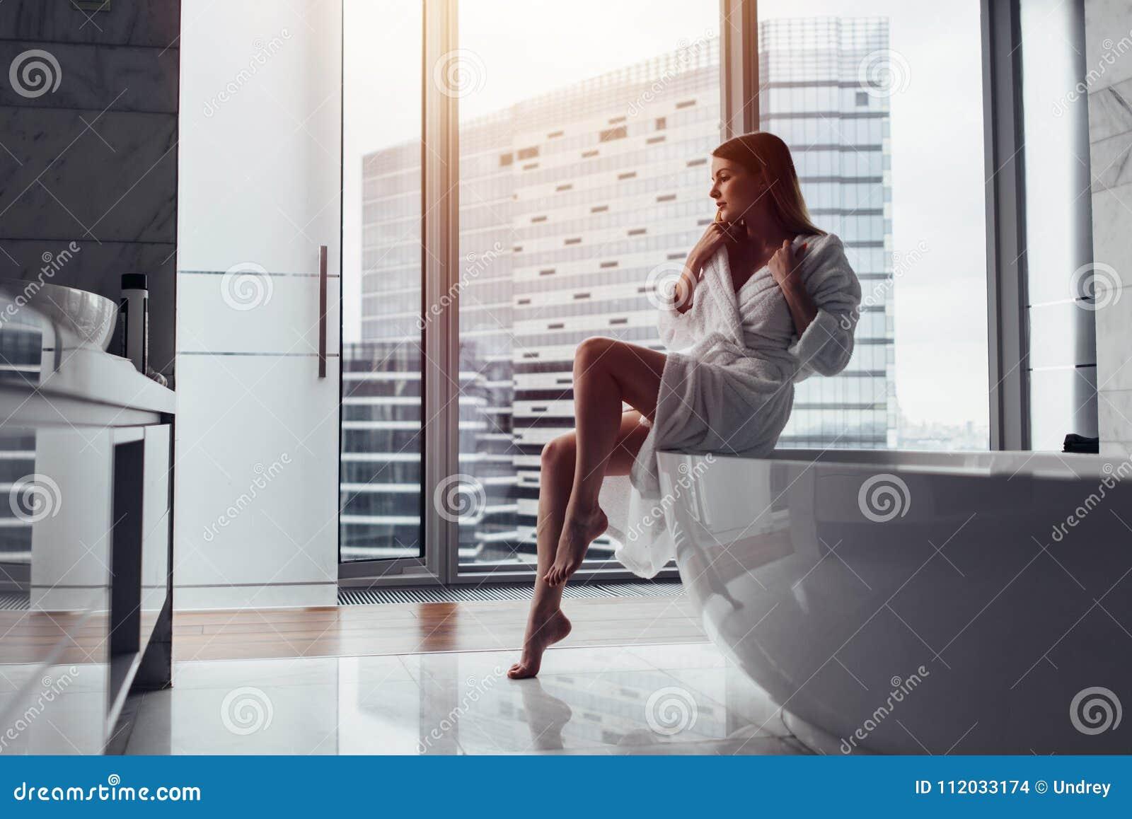 Vista posteriore dell accappatoio bianco d uso della giovane donna che sta nel bagno che guarda fuori la finestra con la vasca in