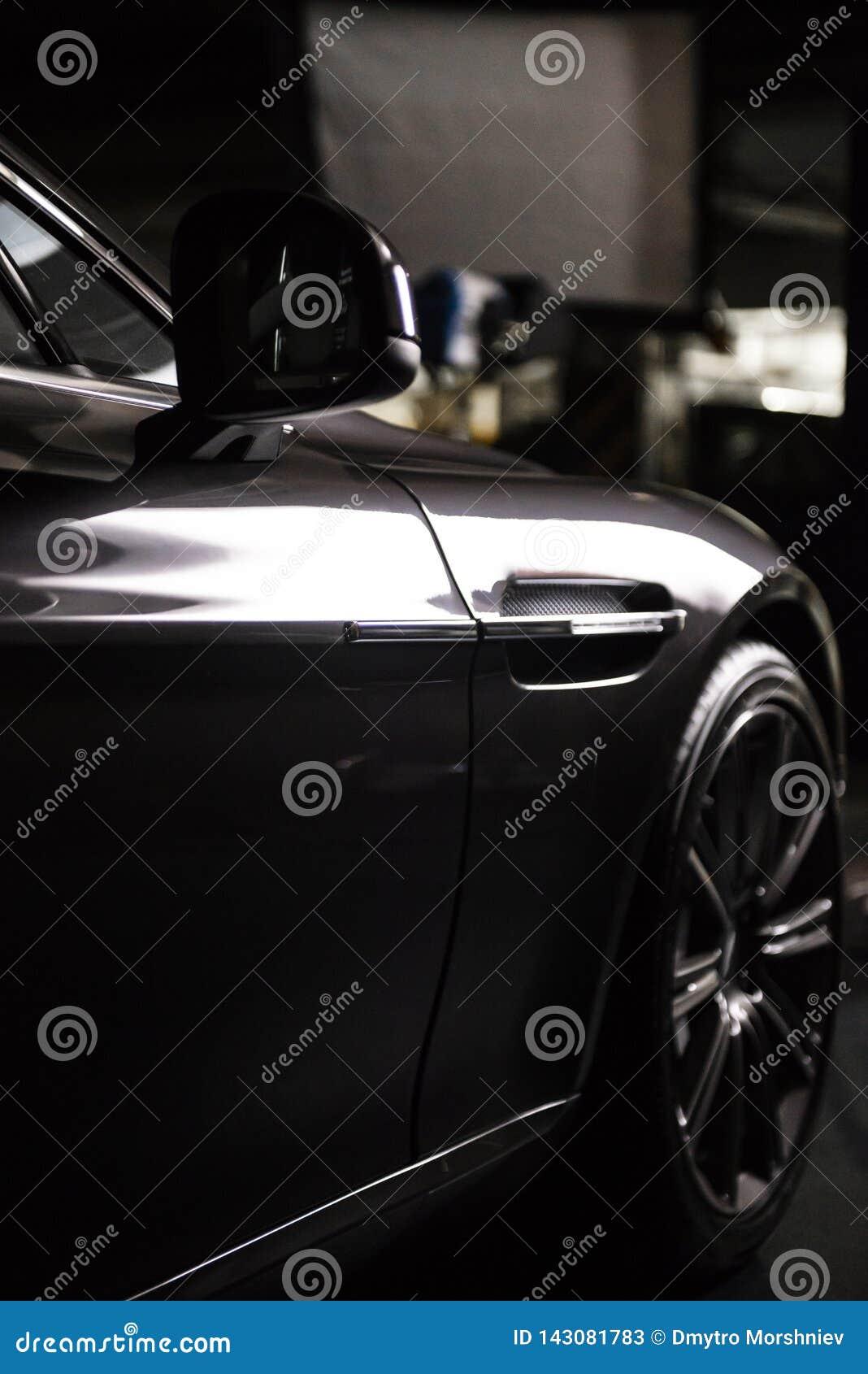 Vista posteriore di un automobile metallica nera grigia di lusso moderna, dettaglio automatico, concetto di cura di automobile ne