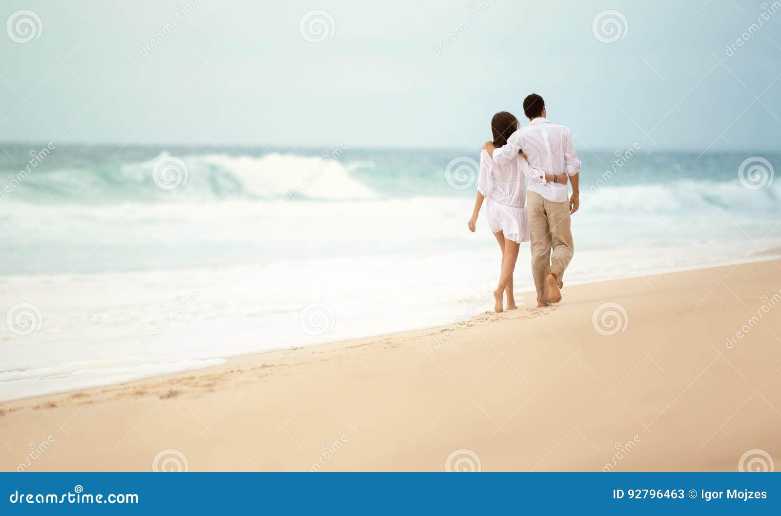 Vista posteriore di una coppia romantica che cammina alla spiaggia