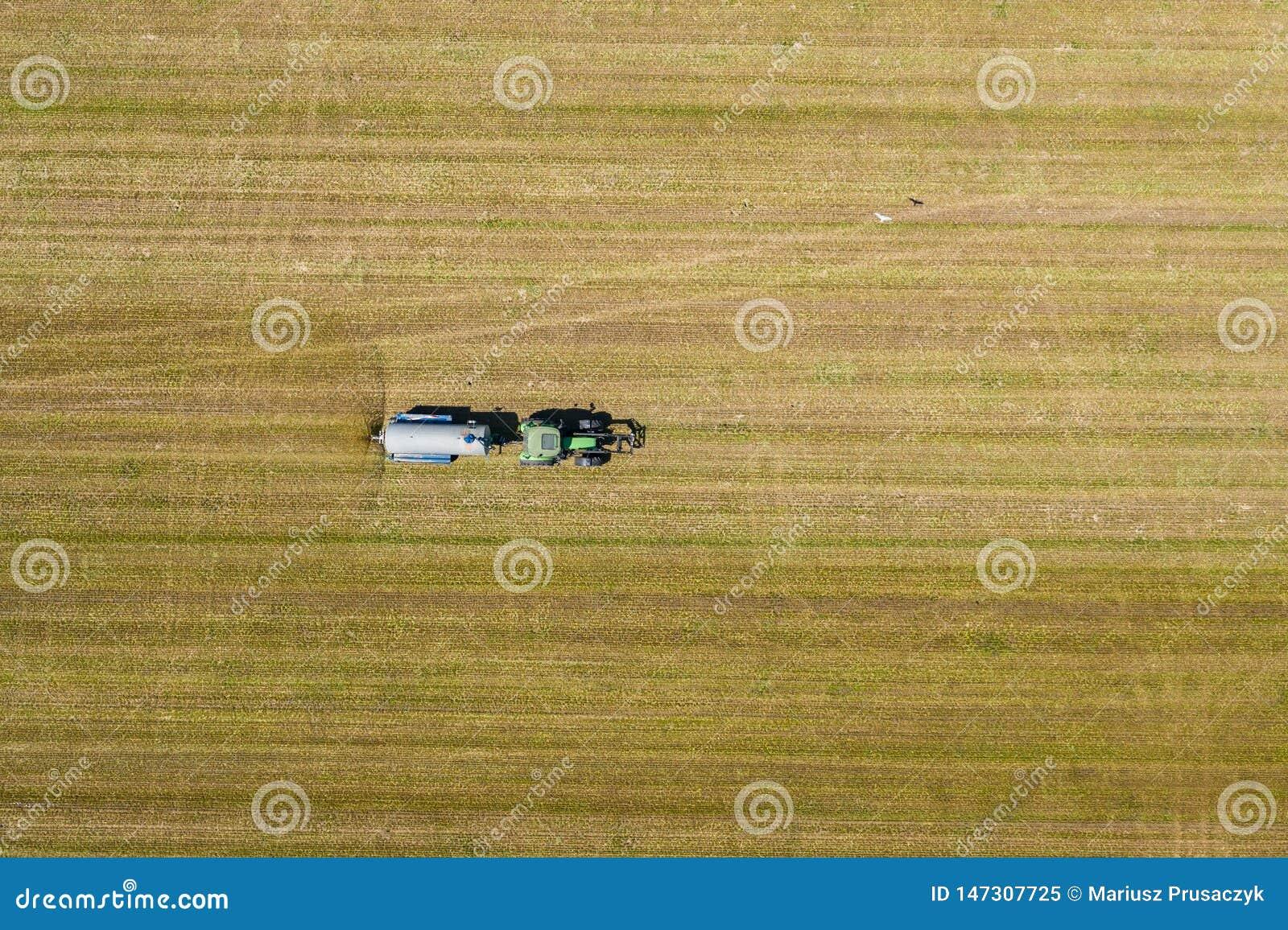 Vista a?rea do trator de cultivo que ara e que pulveriza no campo agricultura Vista de acima Foto capturada com zang?o