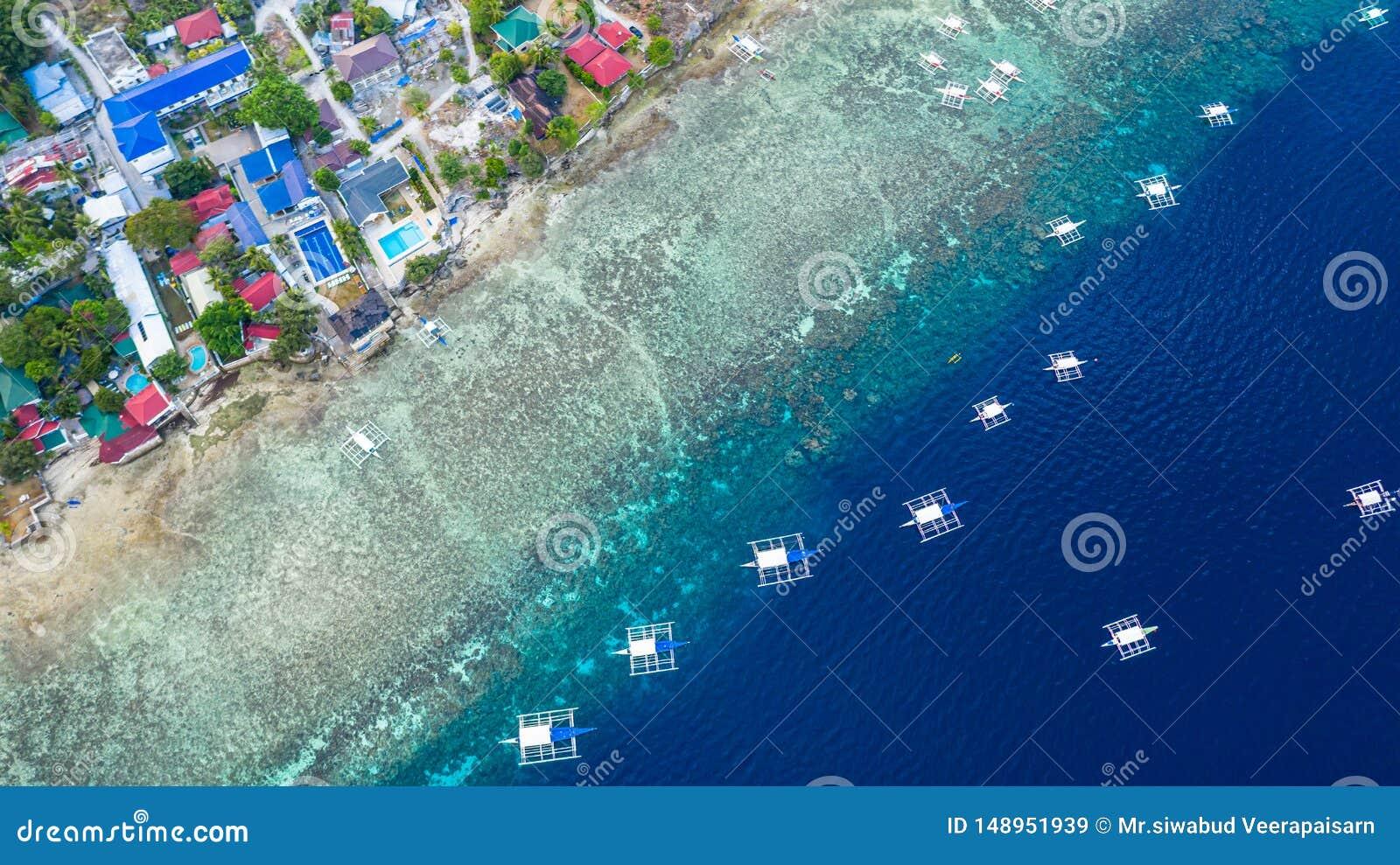 A vista a?rea dos barcos filipinos que flutuam sobre ?guas azuis claras, Moalboal ? um oceano azul limpo profundo e tem muitos lo