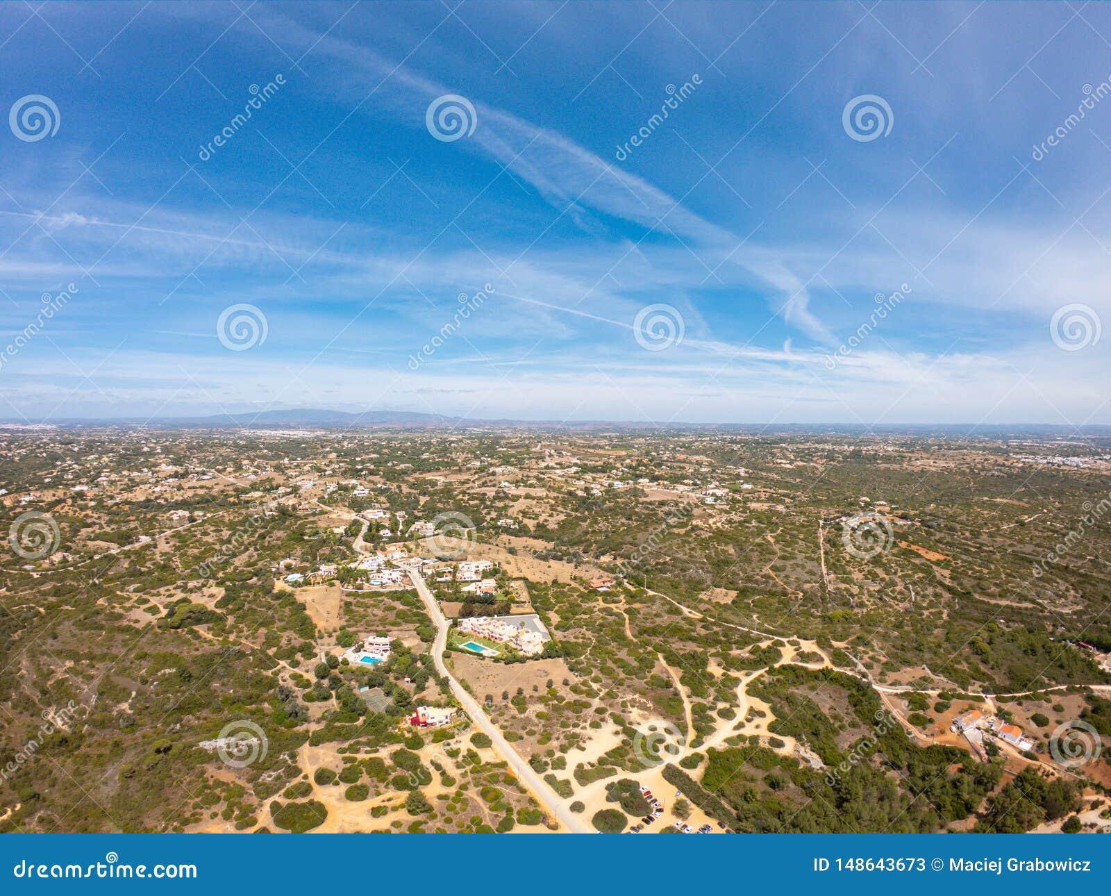 Vista a?rea na vila pequena, campo em Lagoa, Portugal Vista de cima nas casas contra o c?u azul