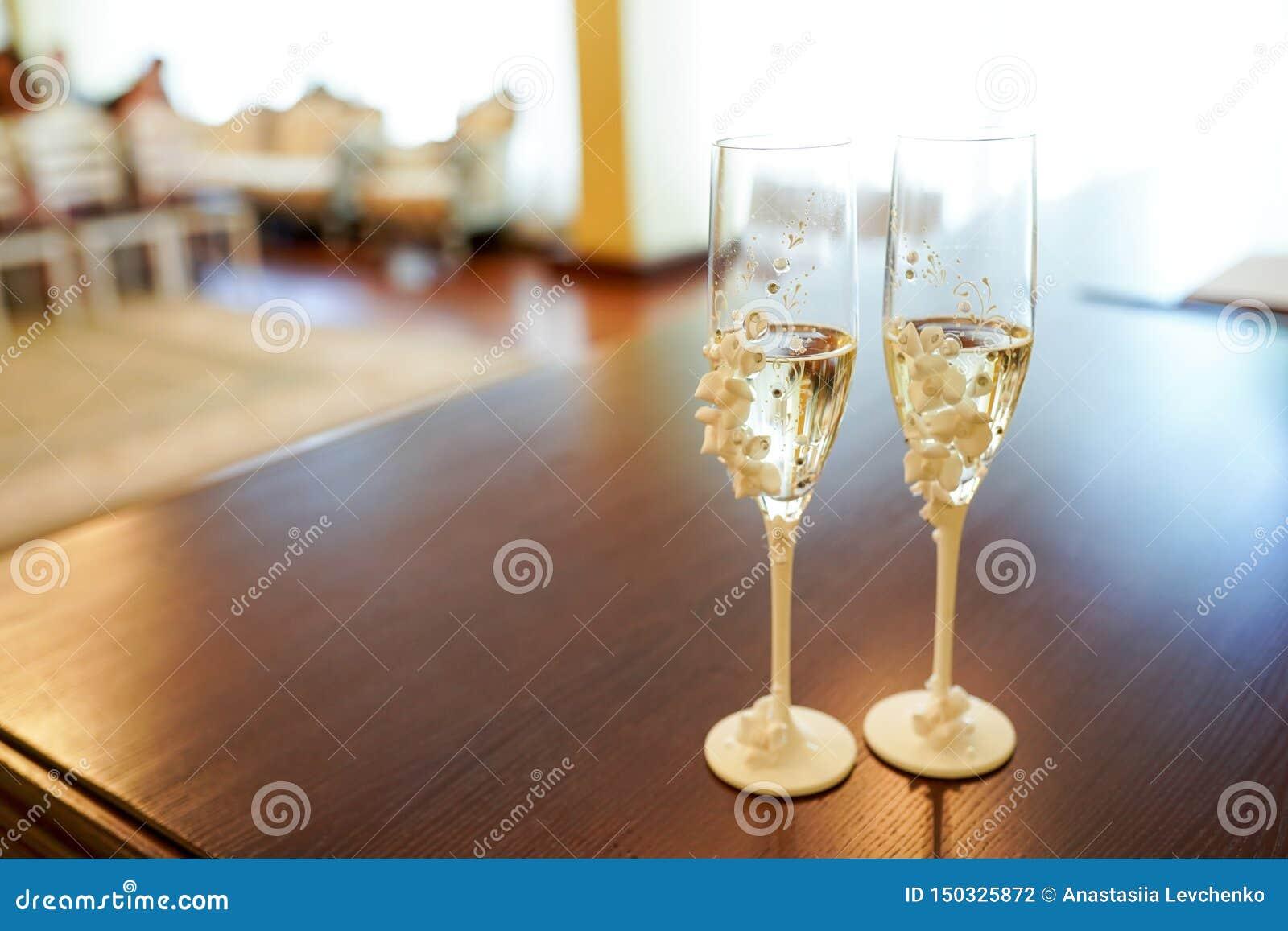 Vista romântica de vidros do casamento com champanhe na tabela escura com espaço da cópia Dois cristais decorados com flores bran