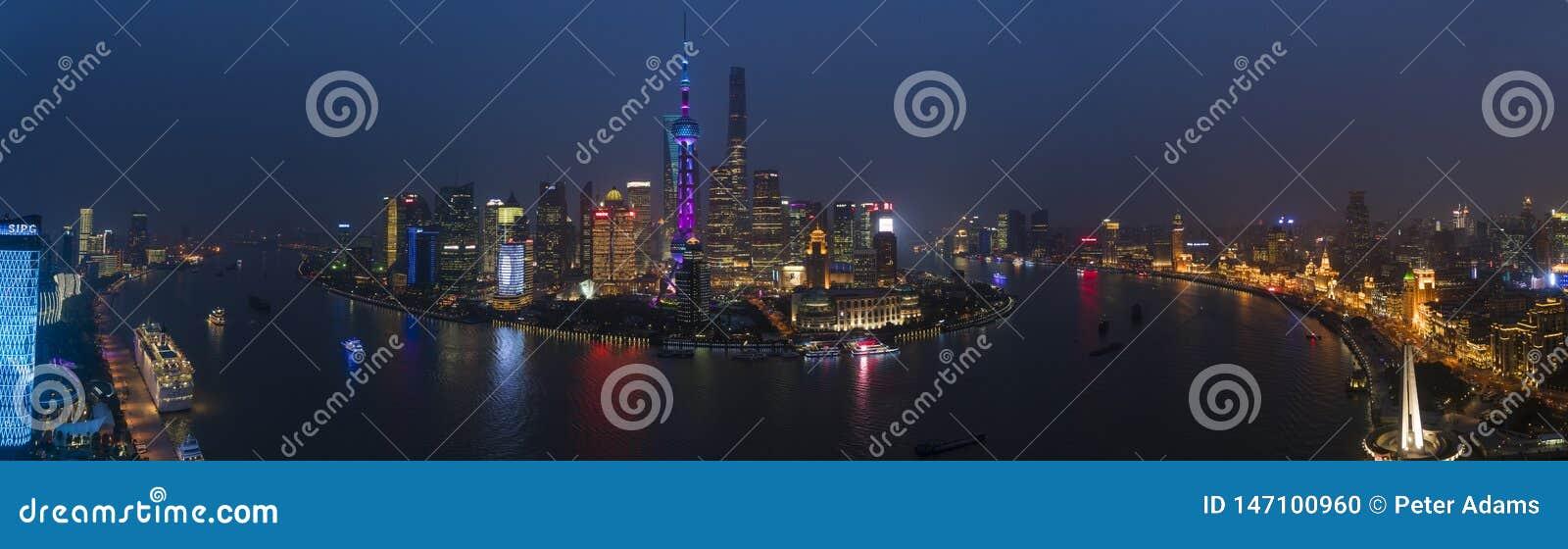Vista sobre a skyline na noite, Shanghai do Rio Huangpu e de Pudong