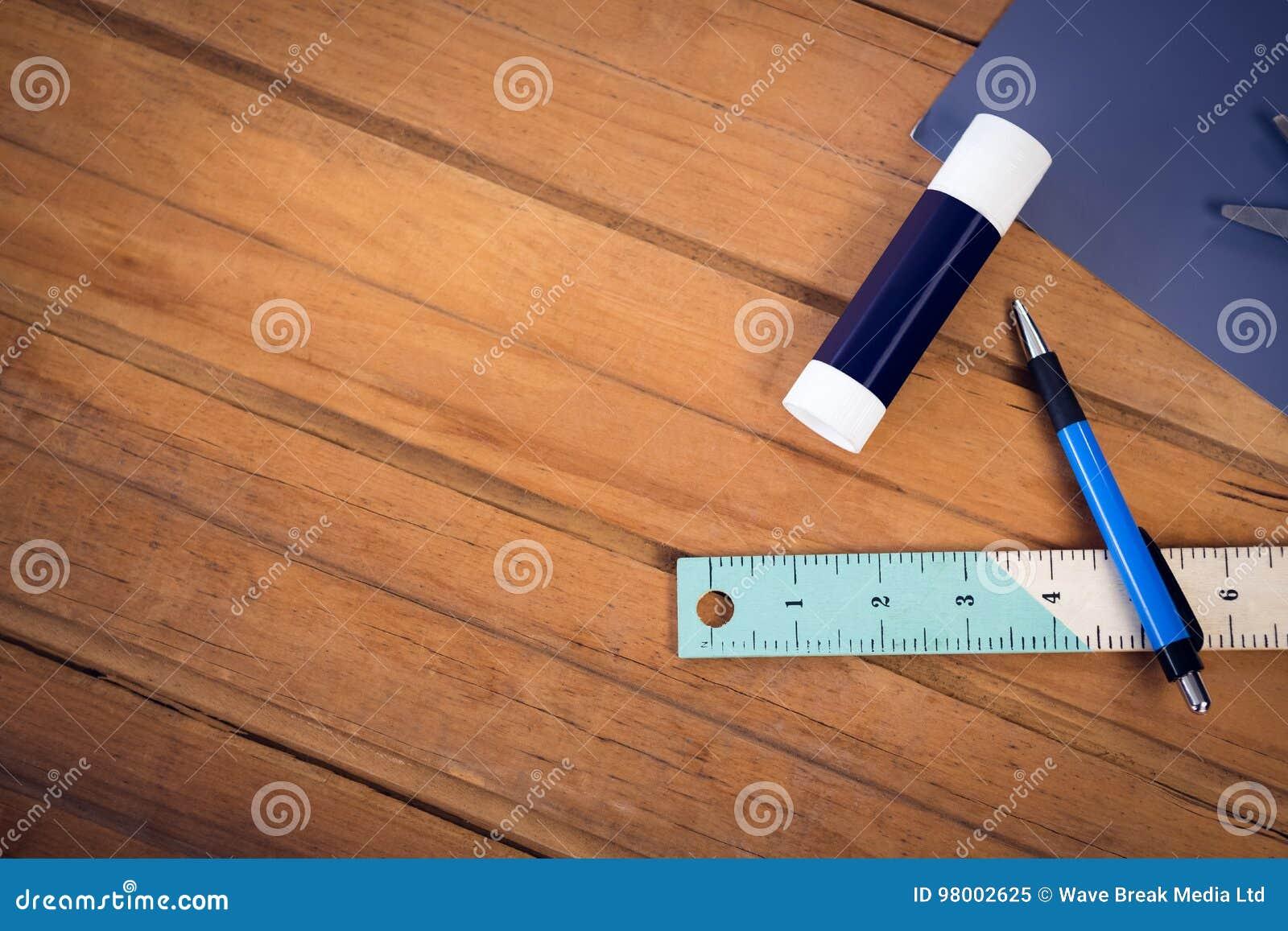 Vista sopraelevata del bastone e della matita della colla con il righello