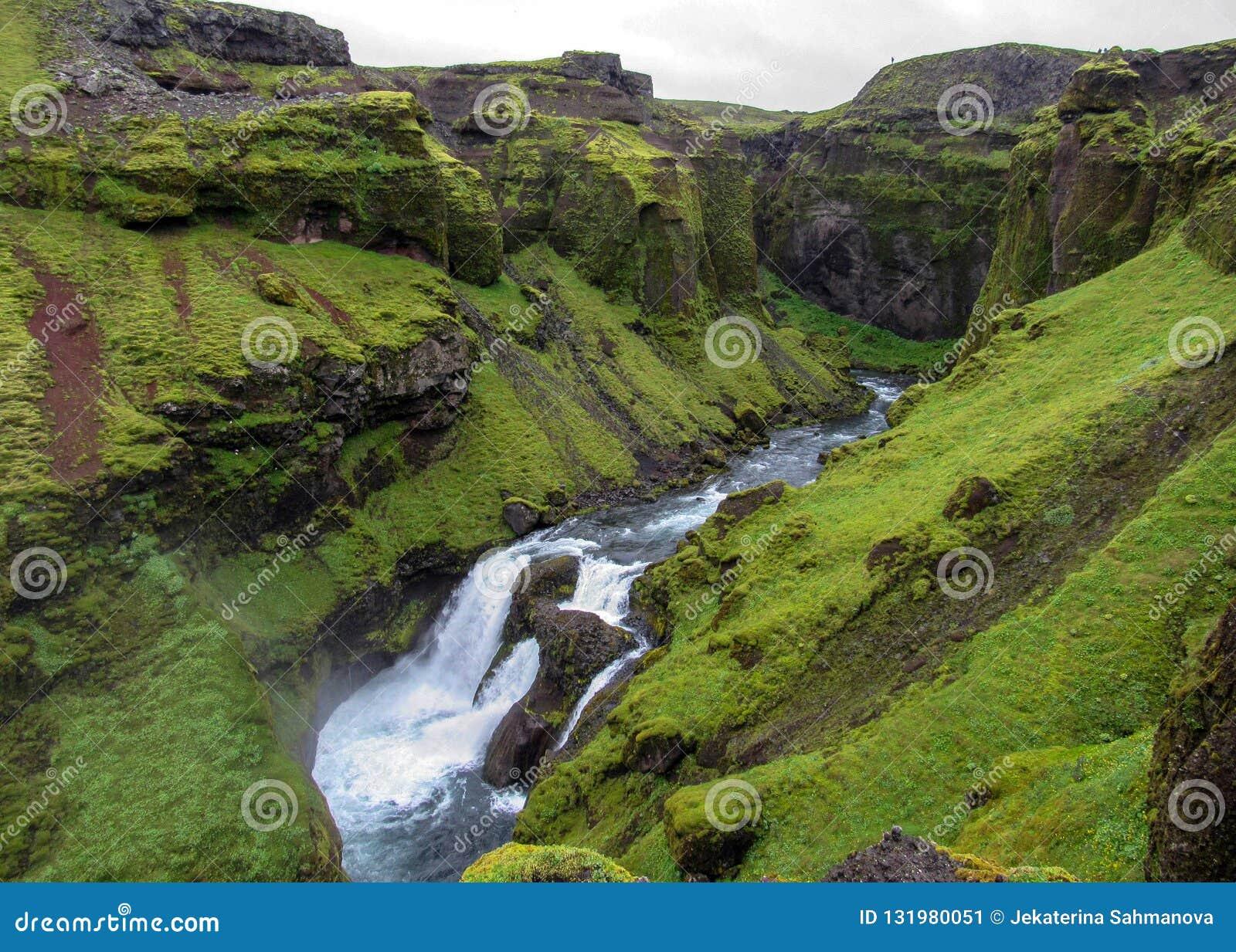 Vista sul fiume di Skoga con la cascata nel giorno di estate piovoso sulla traccia di Fimmvorduhals da Skogar a Thorsmork, altopi