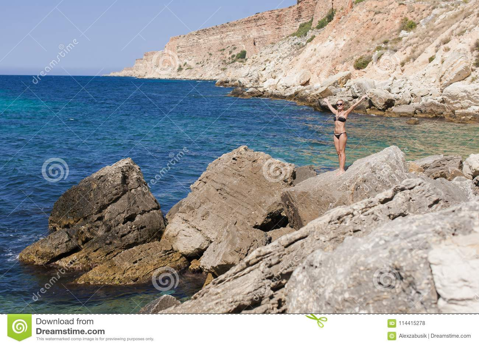 Vista sul mare con la donna bionda abbronzata dai capelli corti in bikini nero