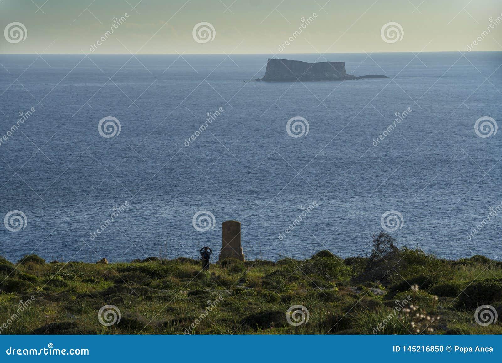 Vista sul mare con una piccola isola ed il monumento in memoria di Sir Walter Norris Congreve a Malta