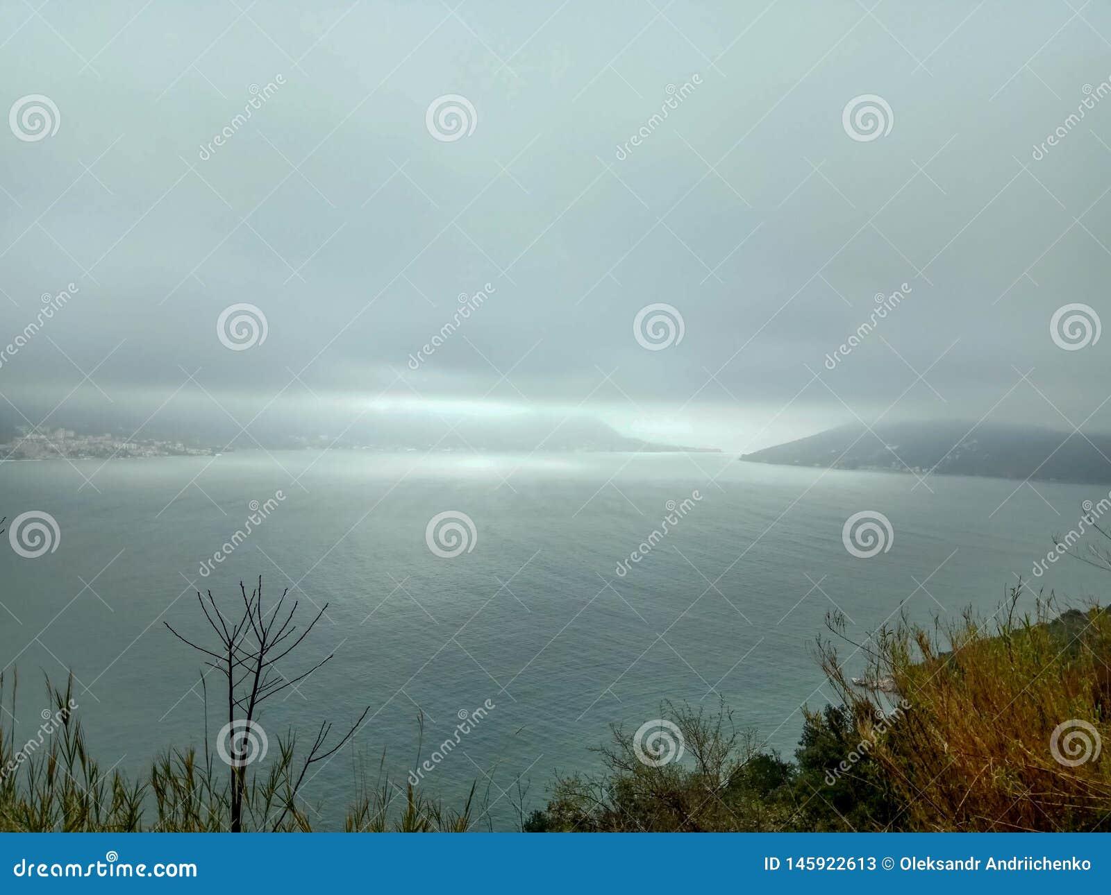 Vista sul mare del tempo - il maltempo arriva a fiumi sul mare, con le onde e le nuvole scure