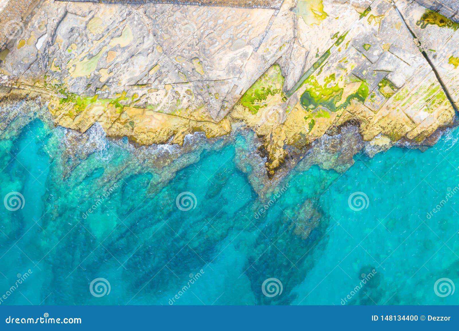 Vista superior aérea de las ondas del mar que golpean rocas en la playa rocosa con las algas verdes con la agua de mar de la turq