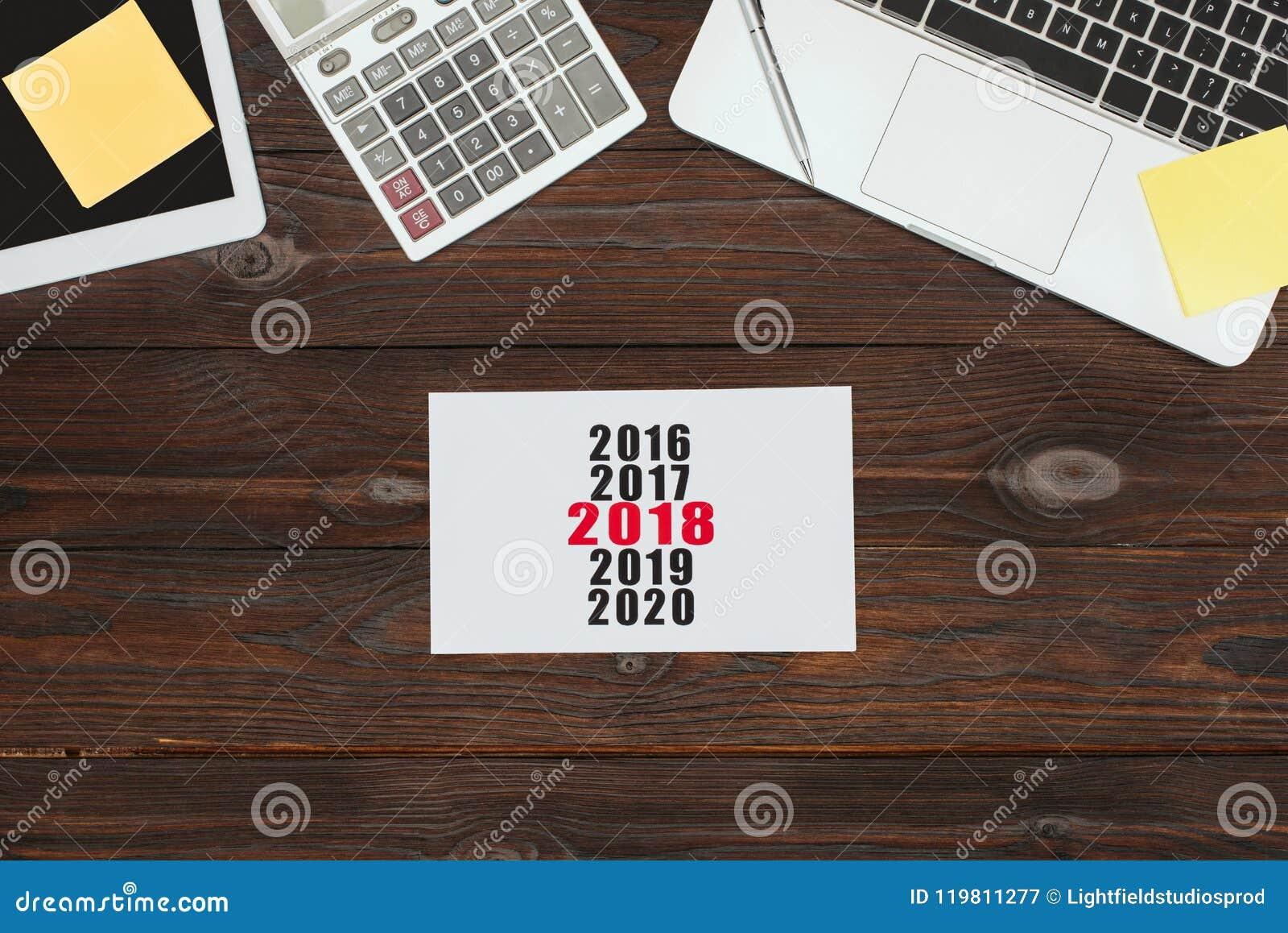 Vista superior de dispositivos, de materiales de oficina y del calendario digitales 2018