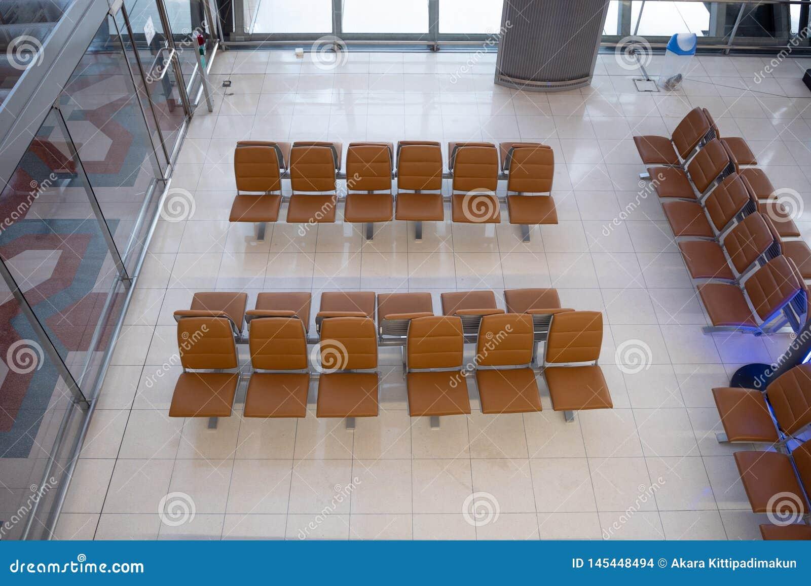 Vista superior de la fila de los asientos marrones para esperar en aeropuerto