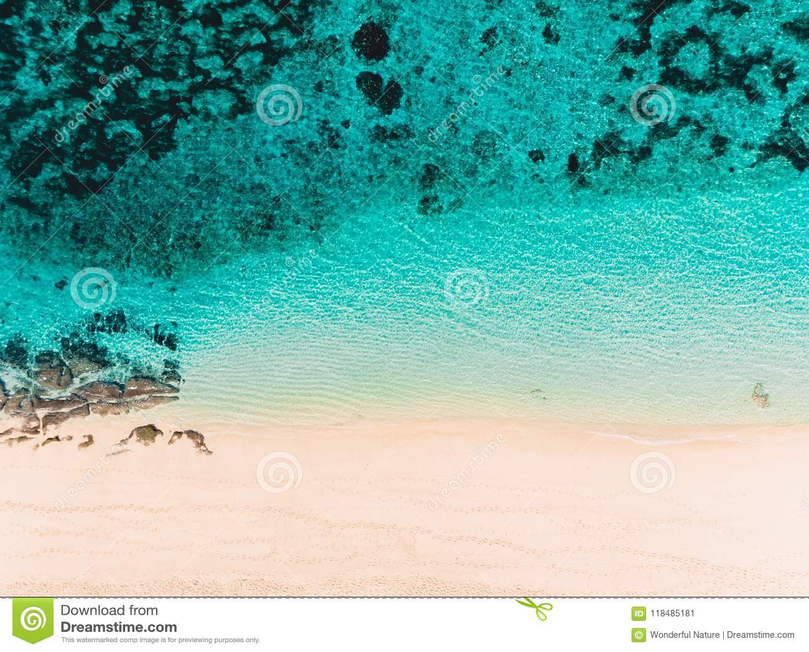 Vista superior de la playa tropical de la arena con agua del océano de la turquesa, tiro aéreo del abejón