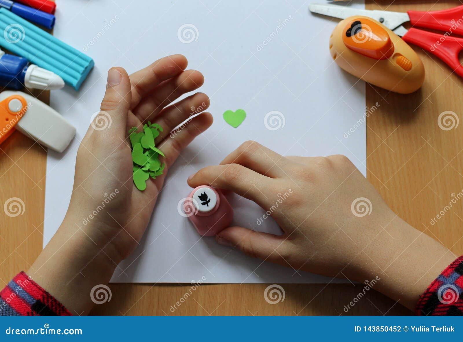 Vista superior de la tabla con una hoja de papel limpia y las manos de un bebé que hacen un regalo El día de madre y el día de la