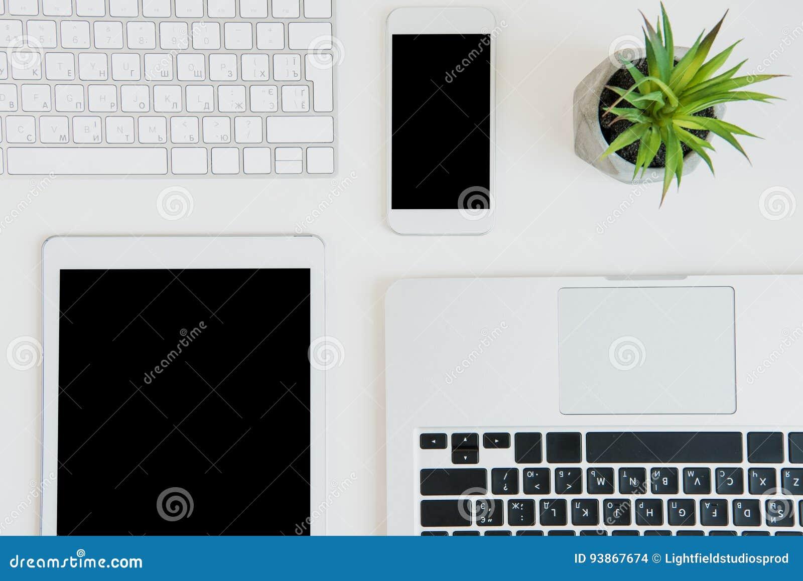 Vista superior de ordenadores portátiles con la tableta y el smartphone digitales en la sobremesa