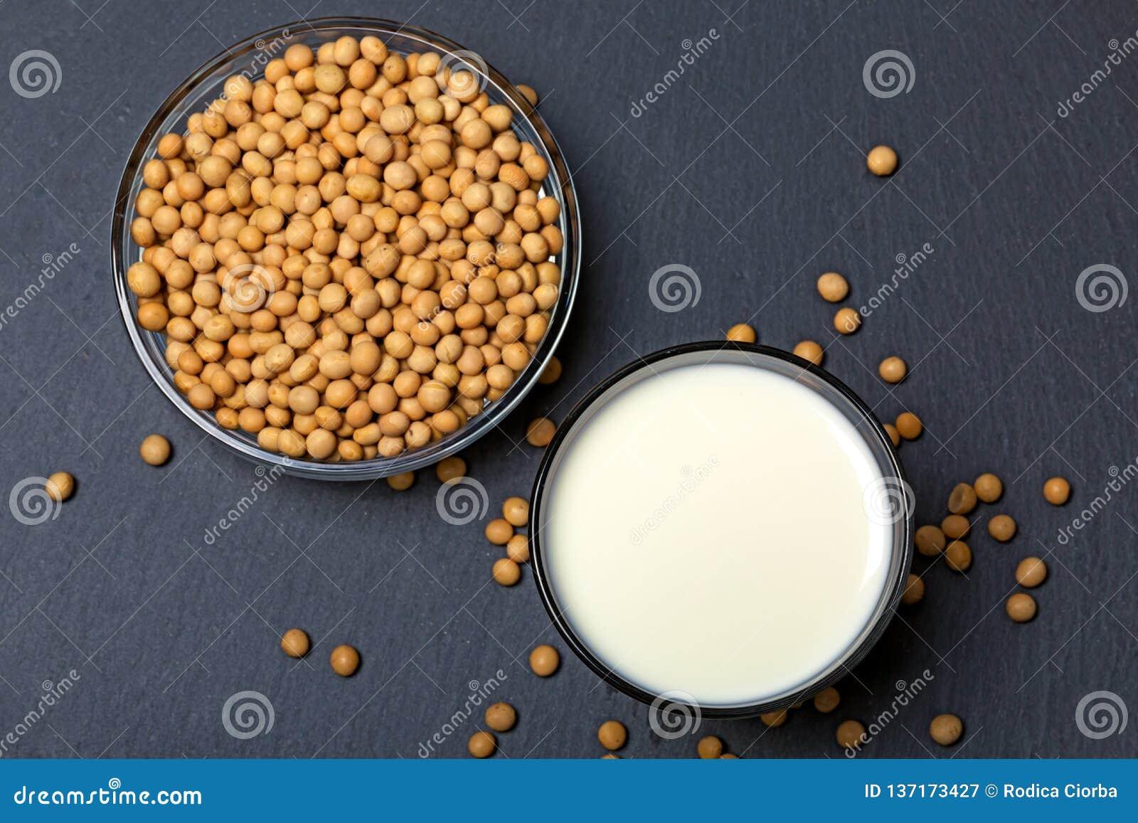 Vista superior de sementes da soja e de vidro do leite no fundo da ardósia