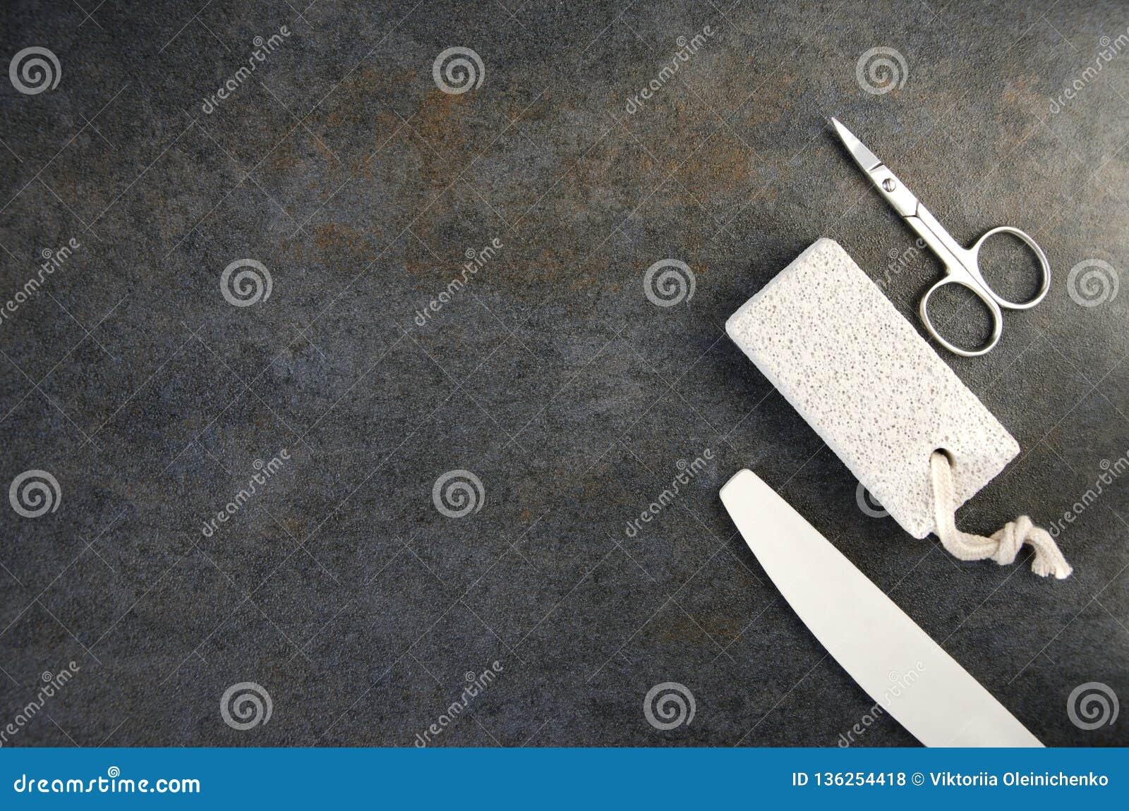 Vista superior de tijeras, del fichero de clavo y de la piedra pómez