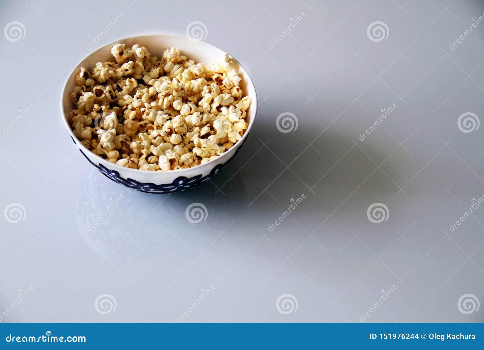 Vista superior de uma pilha da pipoca do caramelo da pipoca em uma placa em uma tabela de vidro