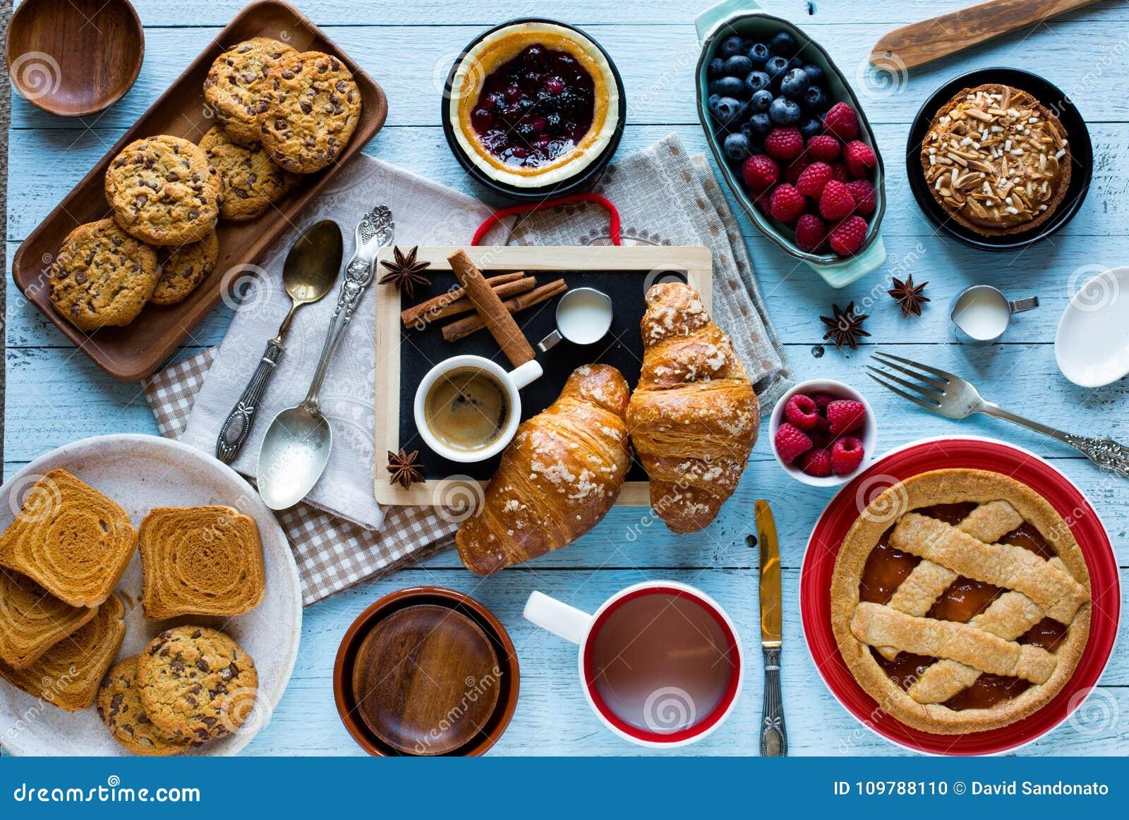 Vista superior de uma tabela de madeira completamente dos bolos, frutos, café, biscoitos