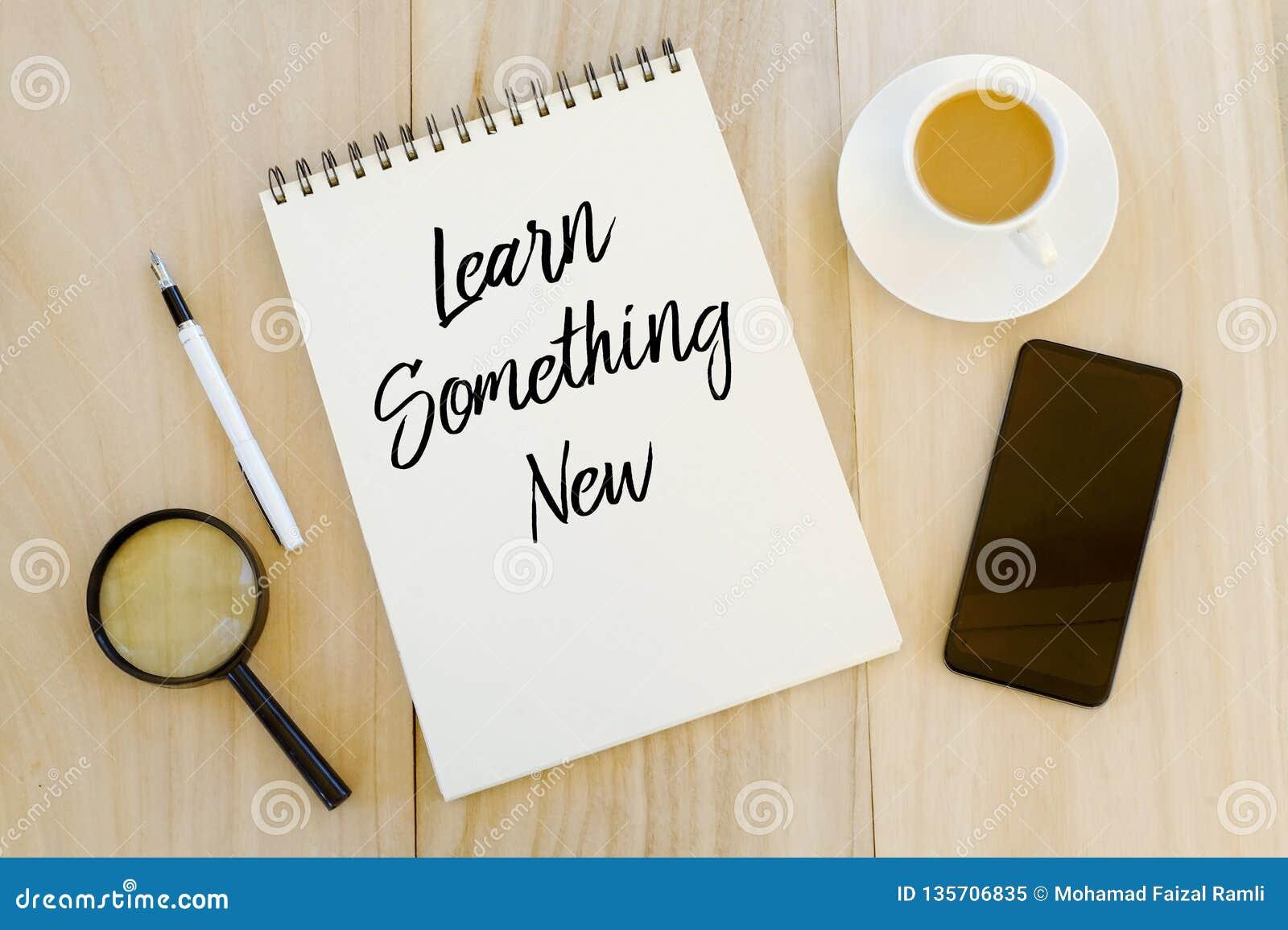 Vista superior de uma xícara de café, de um telefone celular, de uma pena e de um caderno escritos com aprendizagem de algo novo