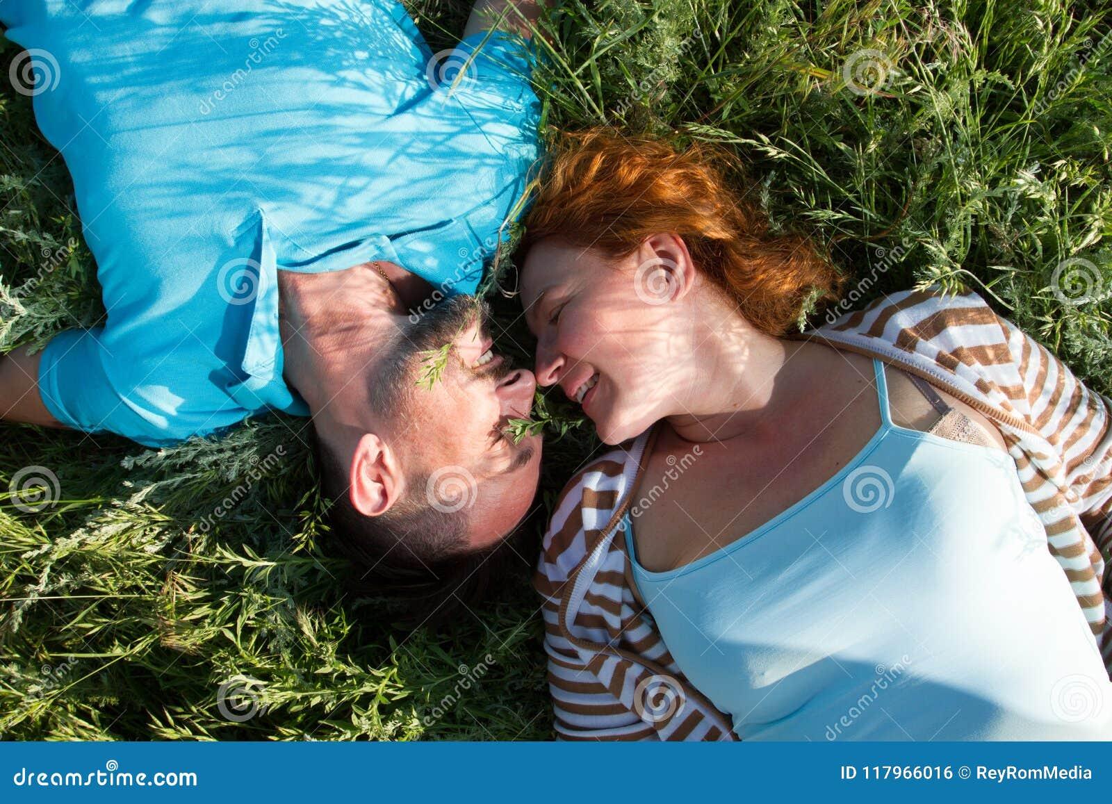 Vista superior de un par con los ojos cerrados en el amor que miente en la hierba verde cara a cara y la nariz para sospechar