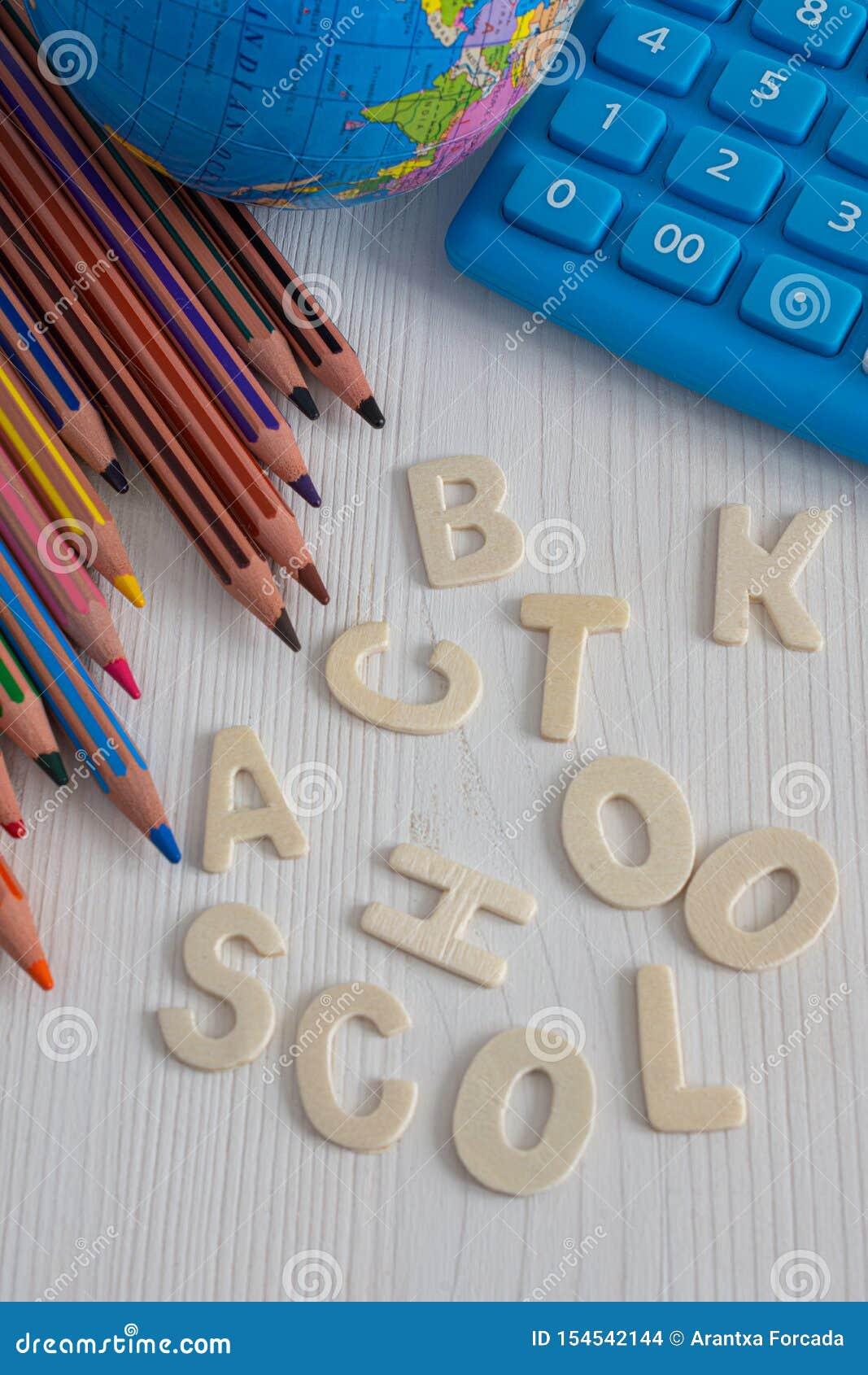 Vista superior de varios lápices coloreados diagonales, bola del mundo y calculadora azul, con las palabras de nuevo a la escuela