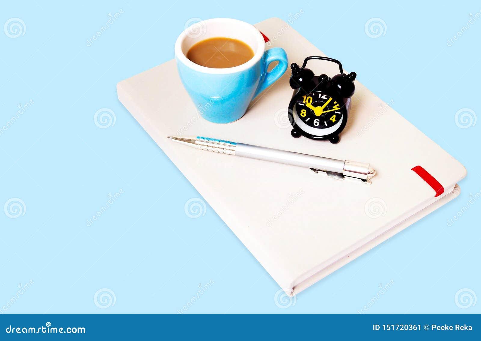 Vista superior del diseño de la plantilla del fondo con la taza de café, el despertador y el cuaderno en el papel azul