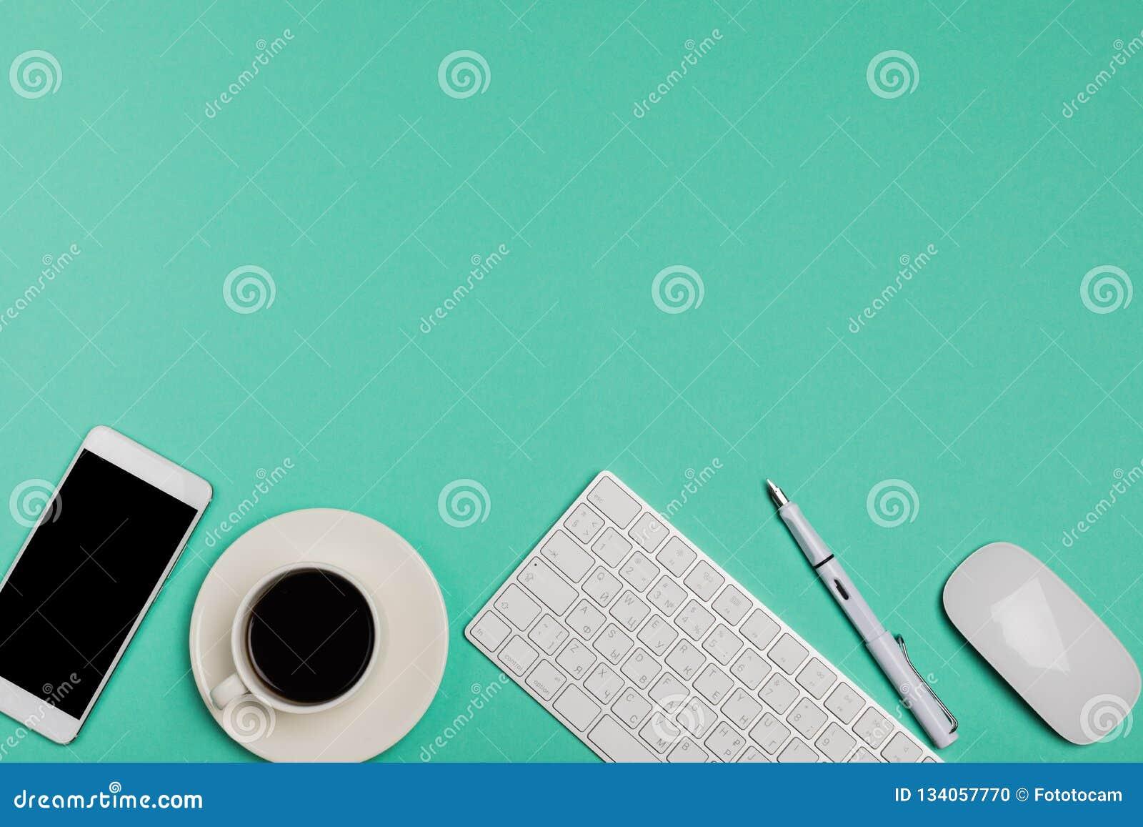 Vista superior del espacio de trabajo del escritorio de oficina con smartphone, el teclado, el café y el ratón en fondo azul con